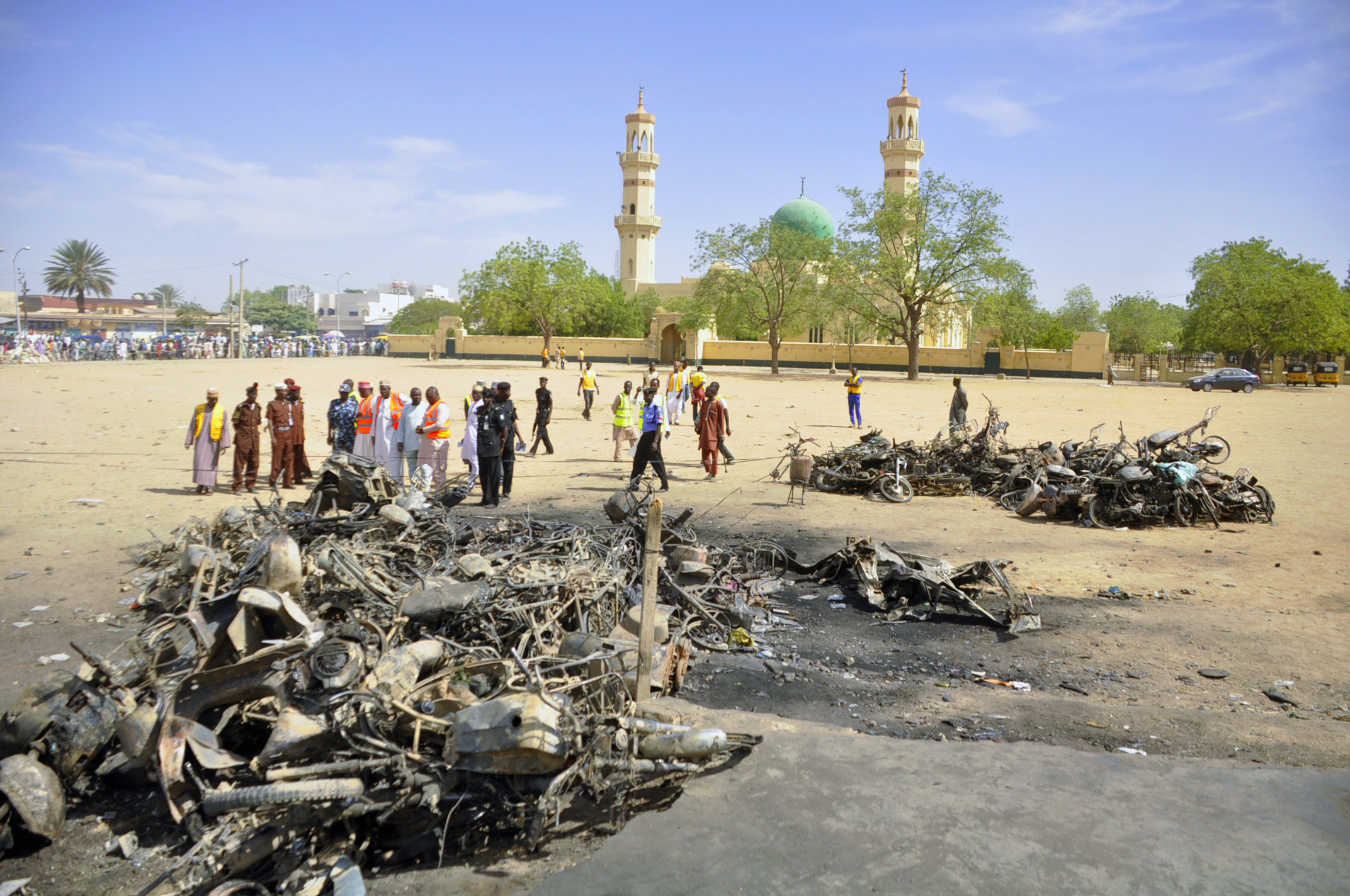 Police and emergency workers investigate a bombing scene in Kano, Nigeris, on November 29, 2014.