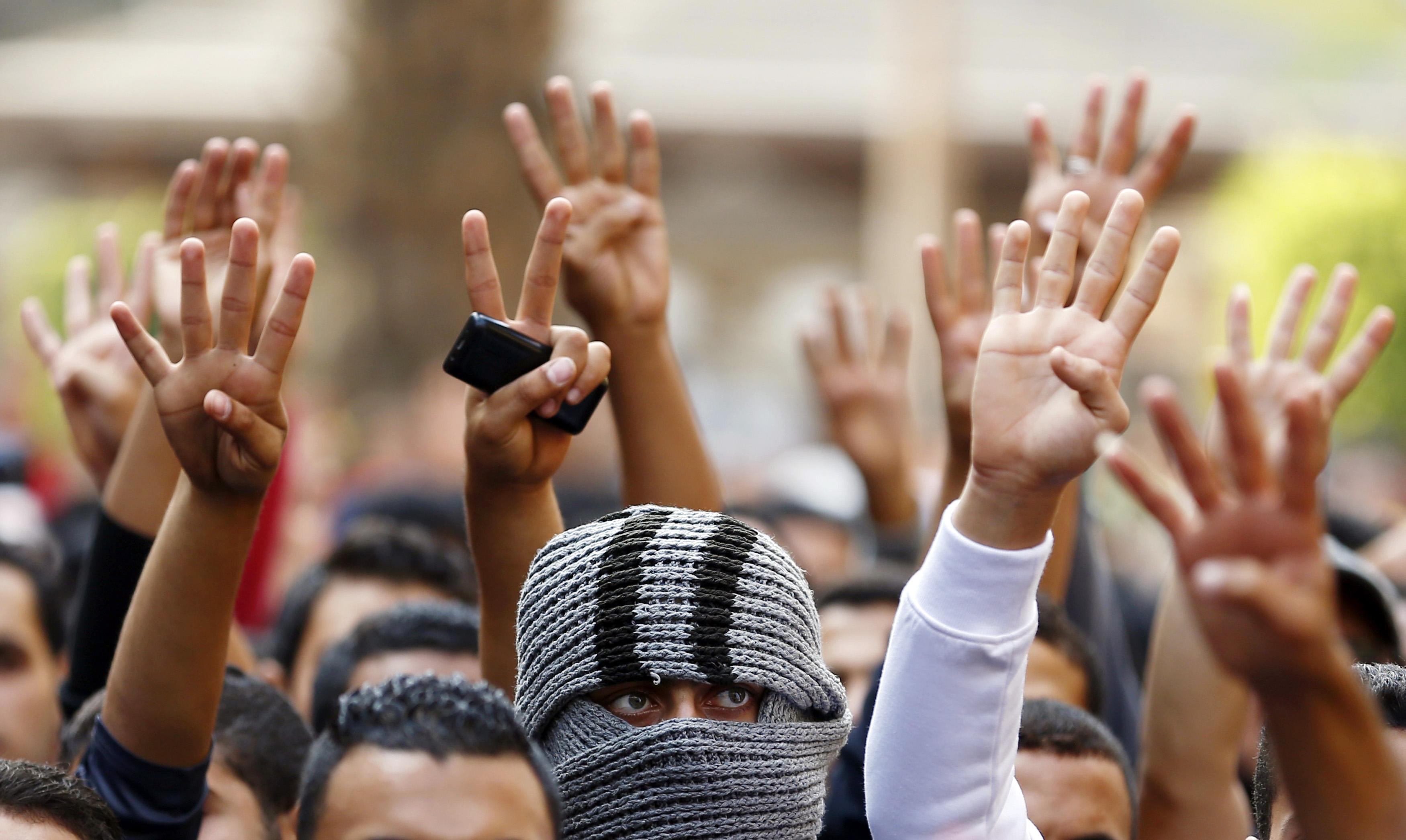 Cairo University students shout slogans against the
