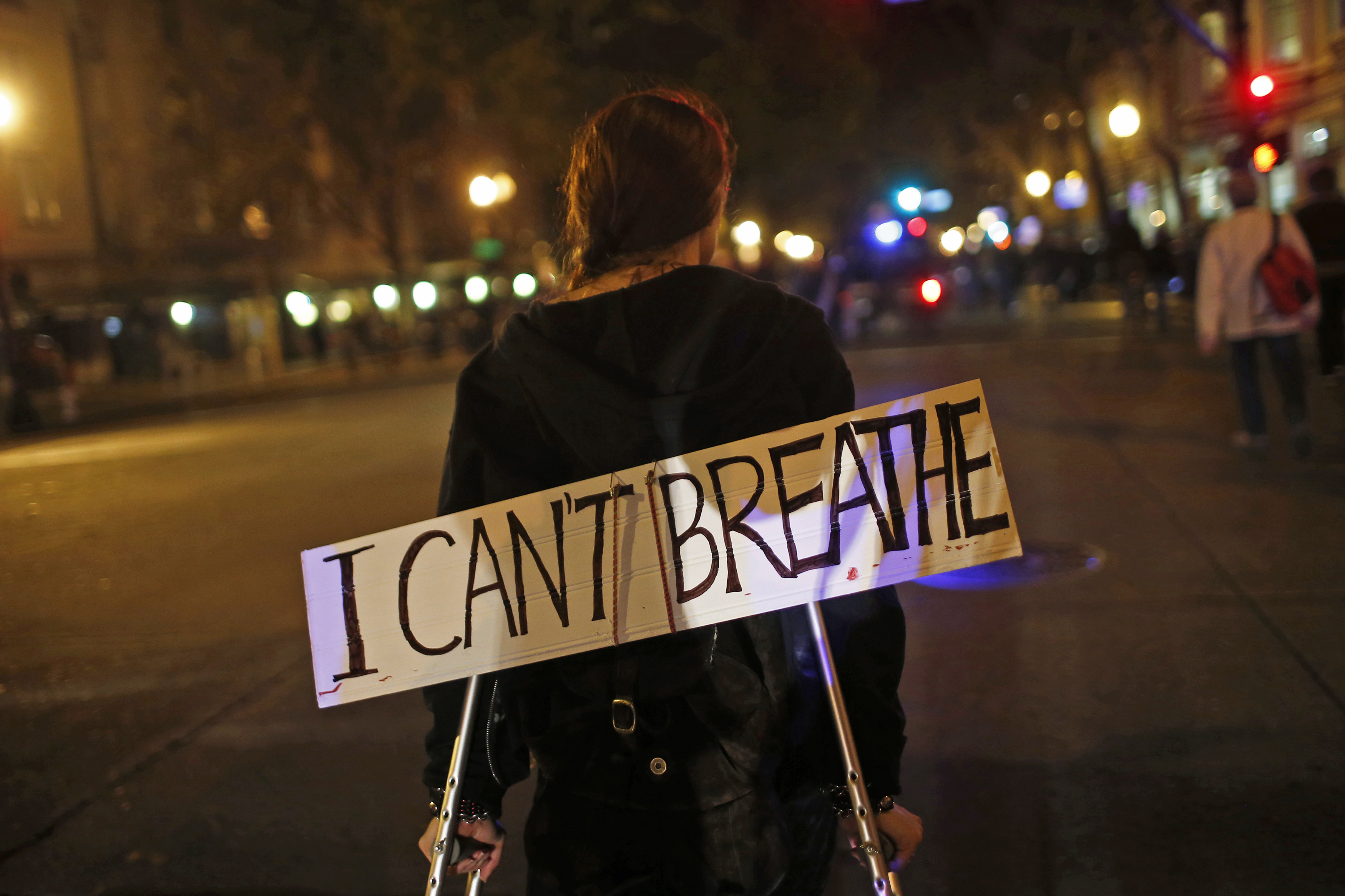 A protester in Oakland, California, on  December 3, 2014, wears a sign during a demonstration against the decision by a New York City grand jury not to indict a police officer in the death of Eric Garner.