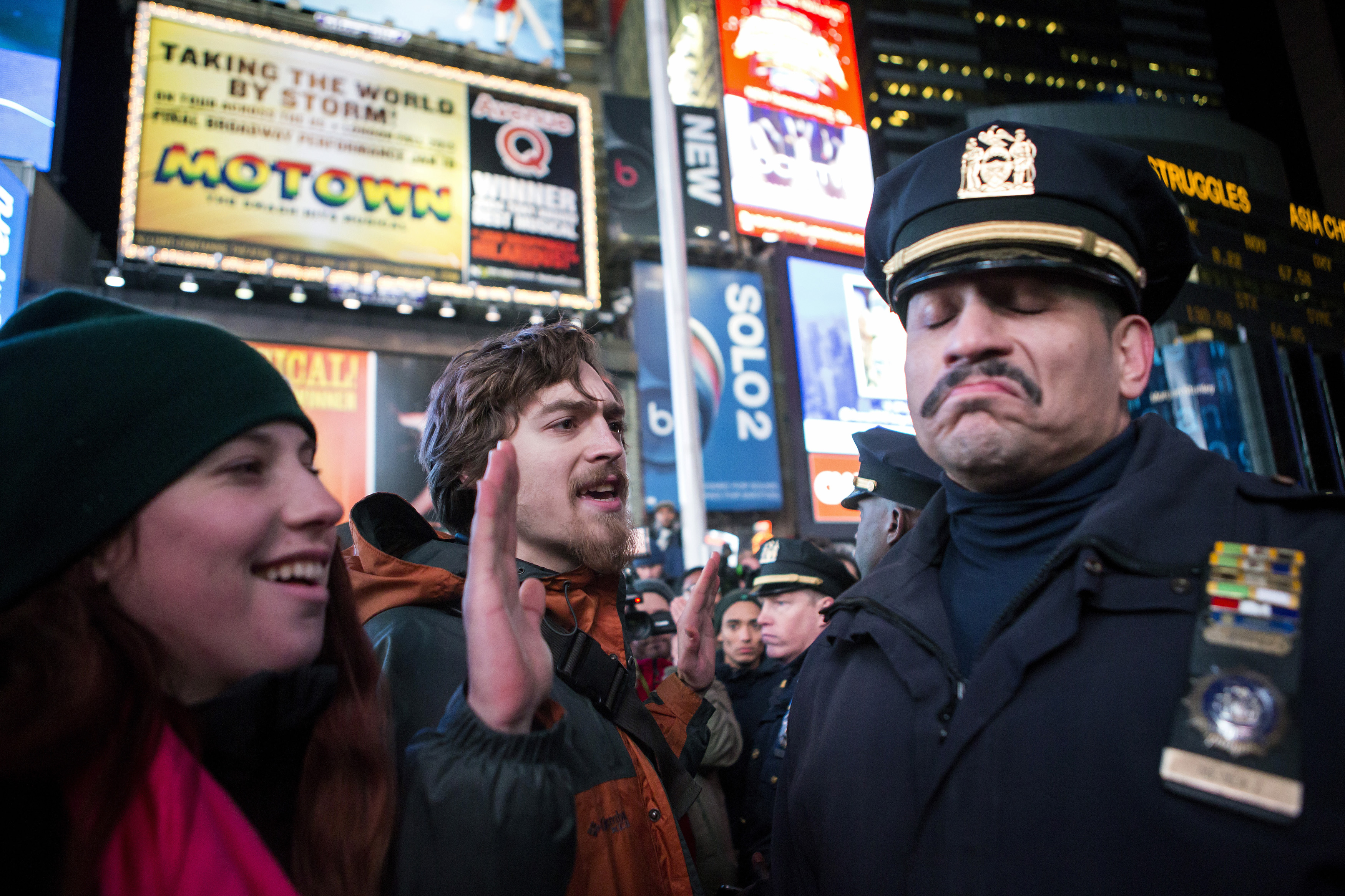 A New York City police officer reacts next to people protesting against the death of Eric Garner during an arrest in July.