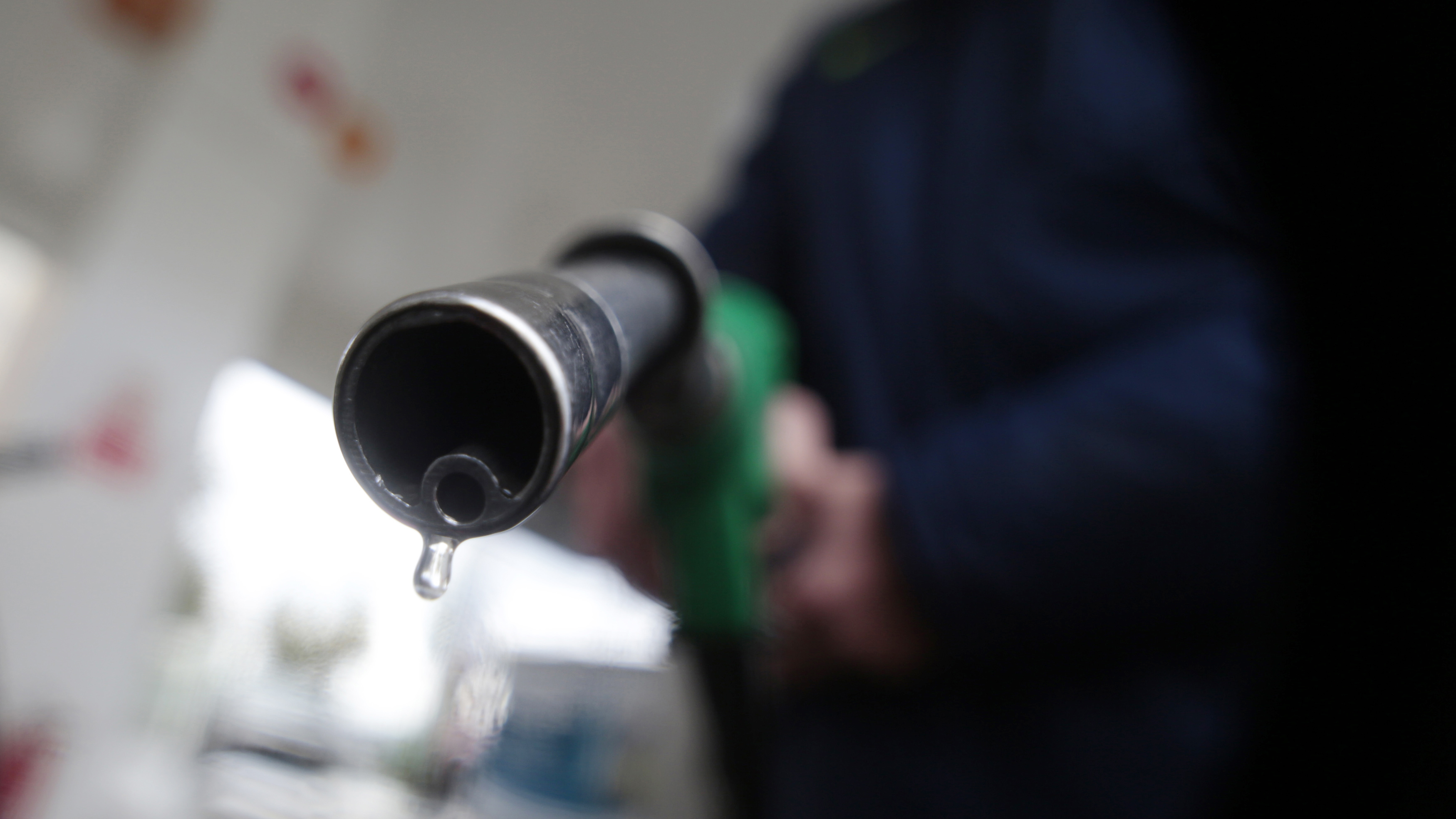 A customer holds a nozzle to fill up his tank in a gasoline station in Nice December 5, 2014.