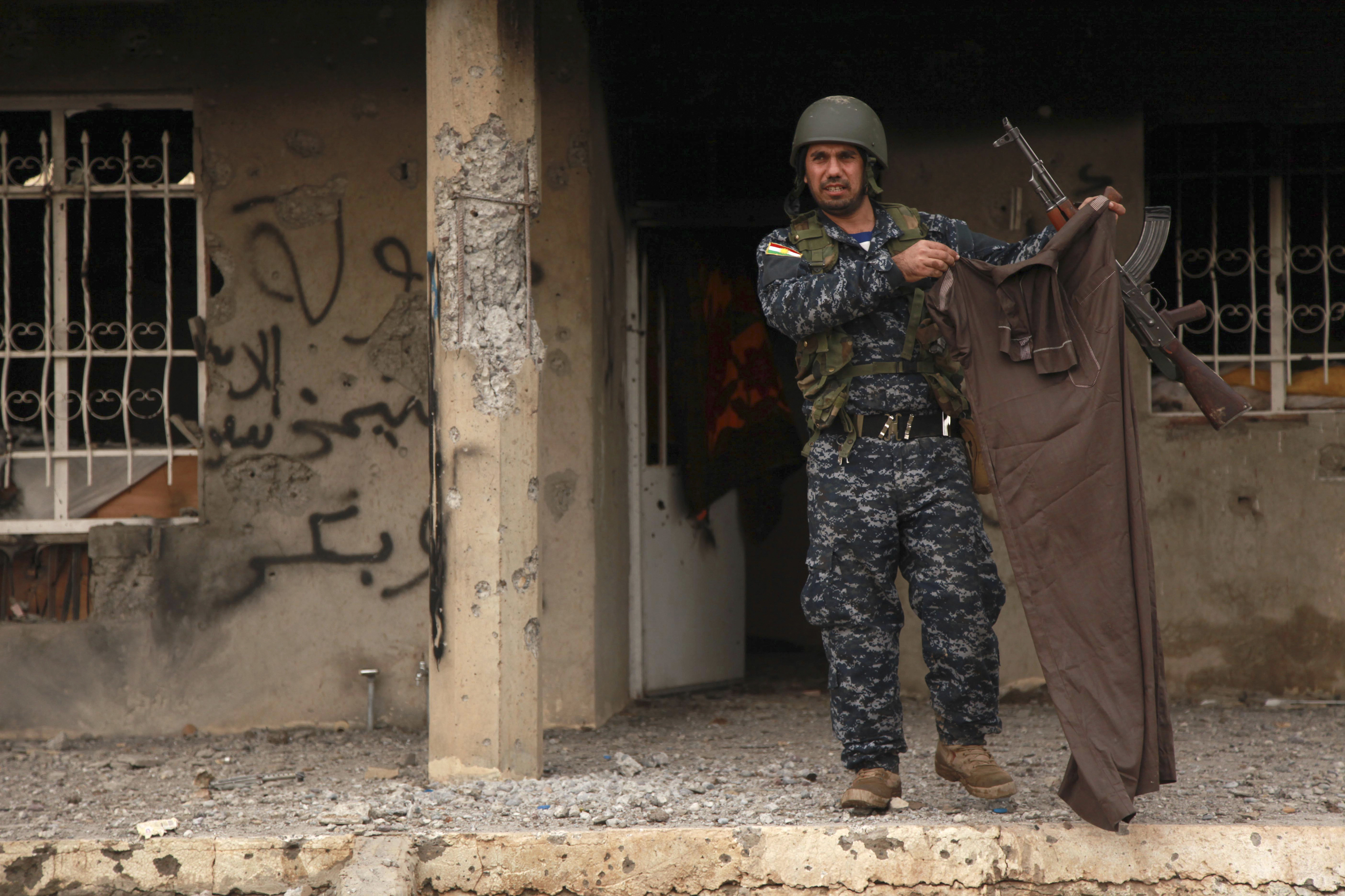 A Kurdish peshmerga fighter holds up a piece of clothing worn by an ISIS fighter on December 18, 2014. Kurdish peshmerga fighters have fought their way to Iraq's Sinjar mountain and freed hundreds of people trapped there by ISIS.