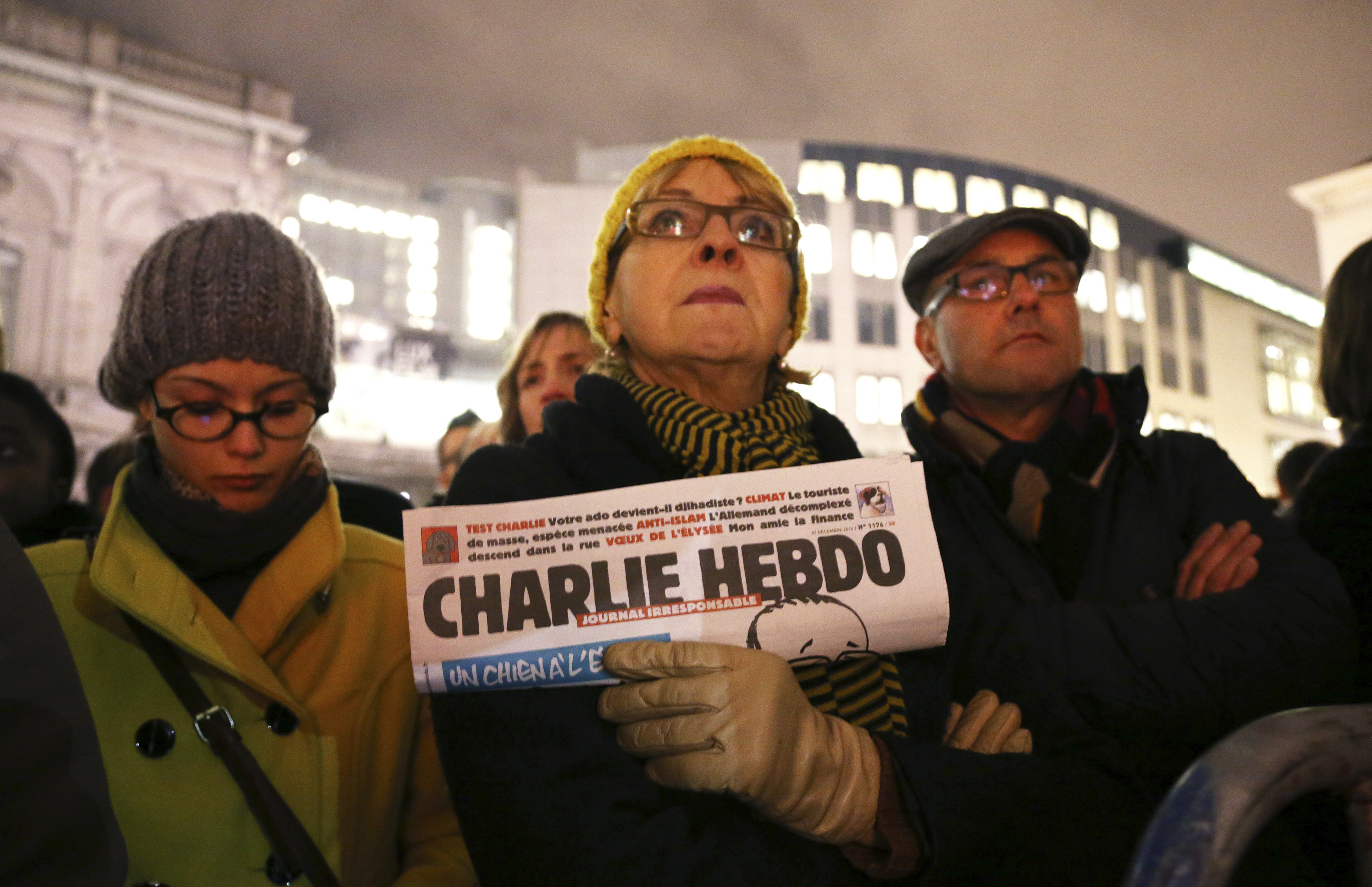 In Brussels, a woman holds a copy of Charlie Hebdo to pay tribute to the victims of a shooting at the offices of the weekly satirical magazine in Paris on January 7, 2015.