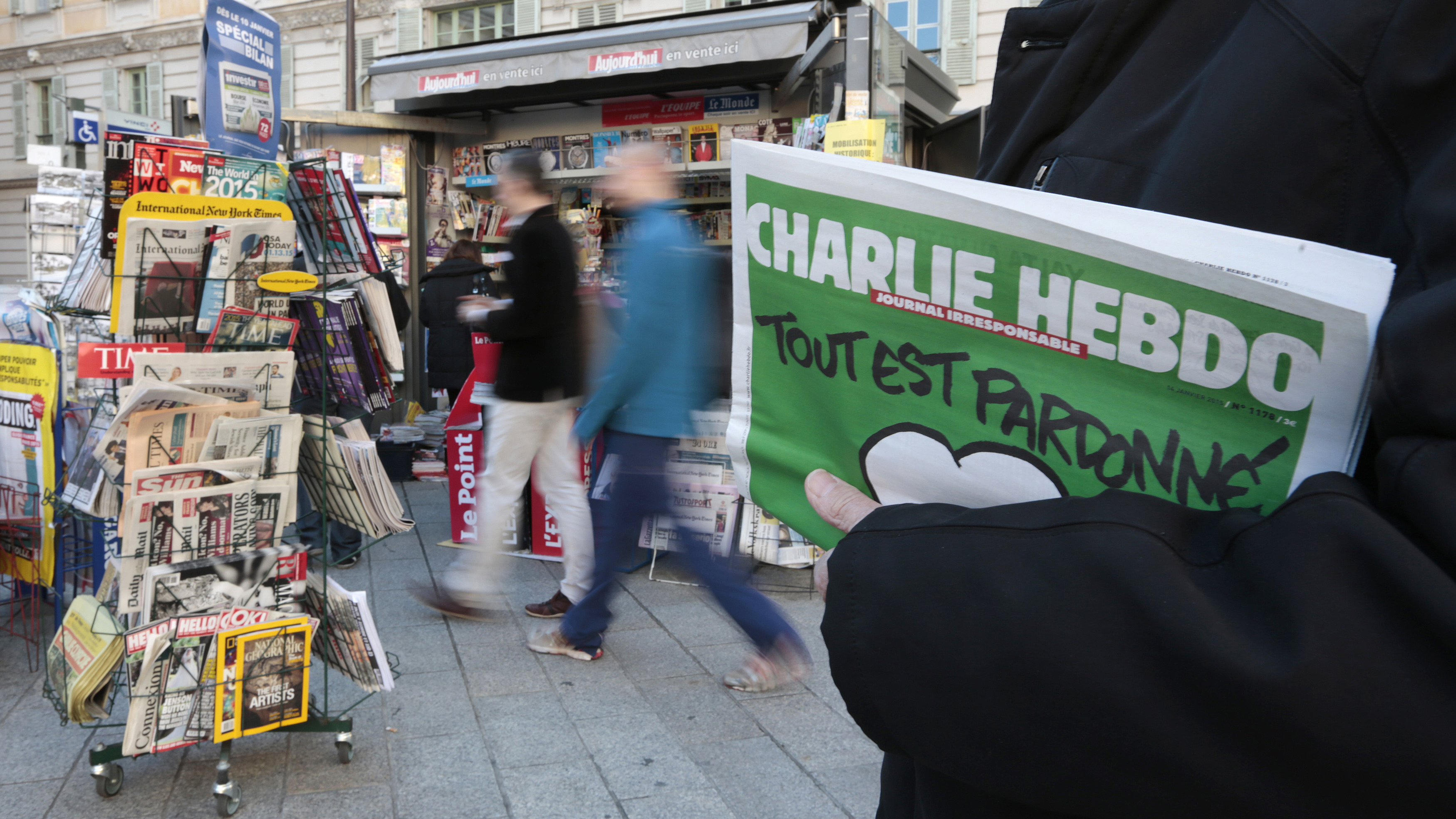 """A man holds the new issue of satirical French weekly Charlie Hebdo, entitled """"Tout est pardonné"""" (""""All is forgiven""""), at a kiosk in Nice on January 14, 2015."""