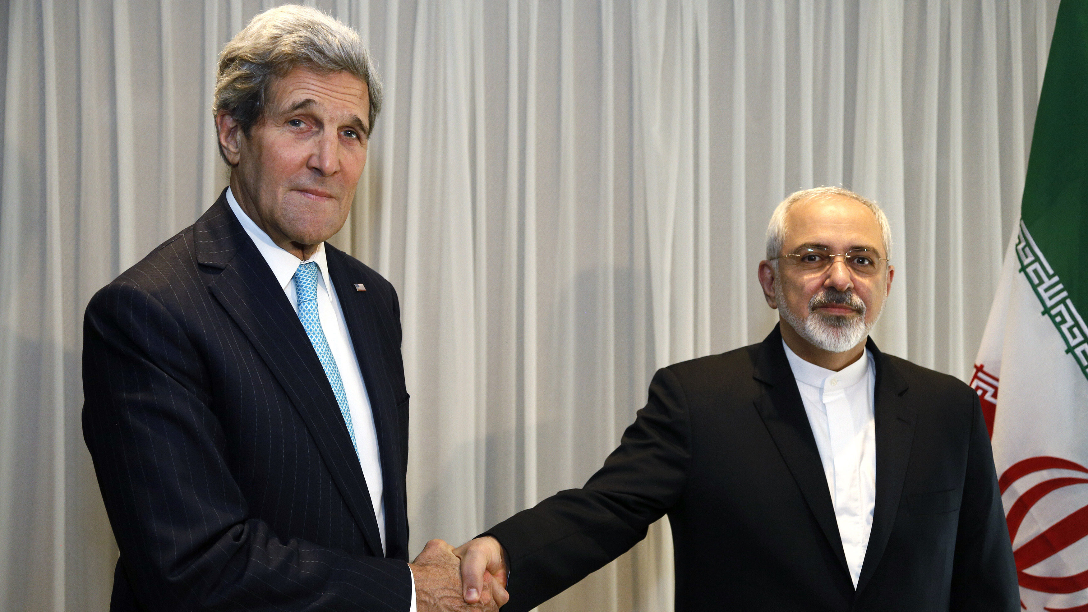 US Secretary of State John Kerry shakes hands with Iranian Foreign Minister Mohammad Javad Zarif before a meeting in Geneva on January 14, 2015.