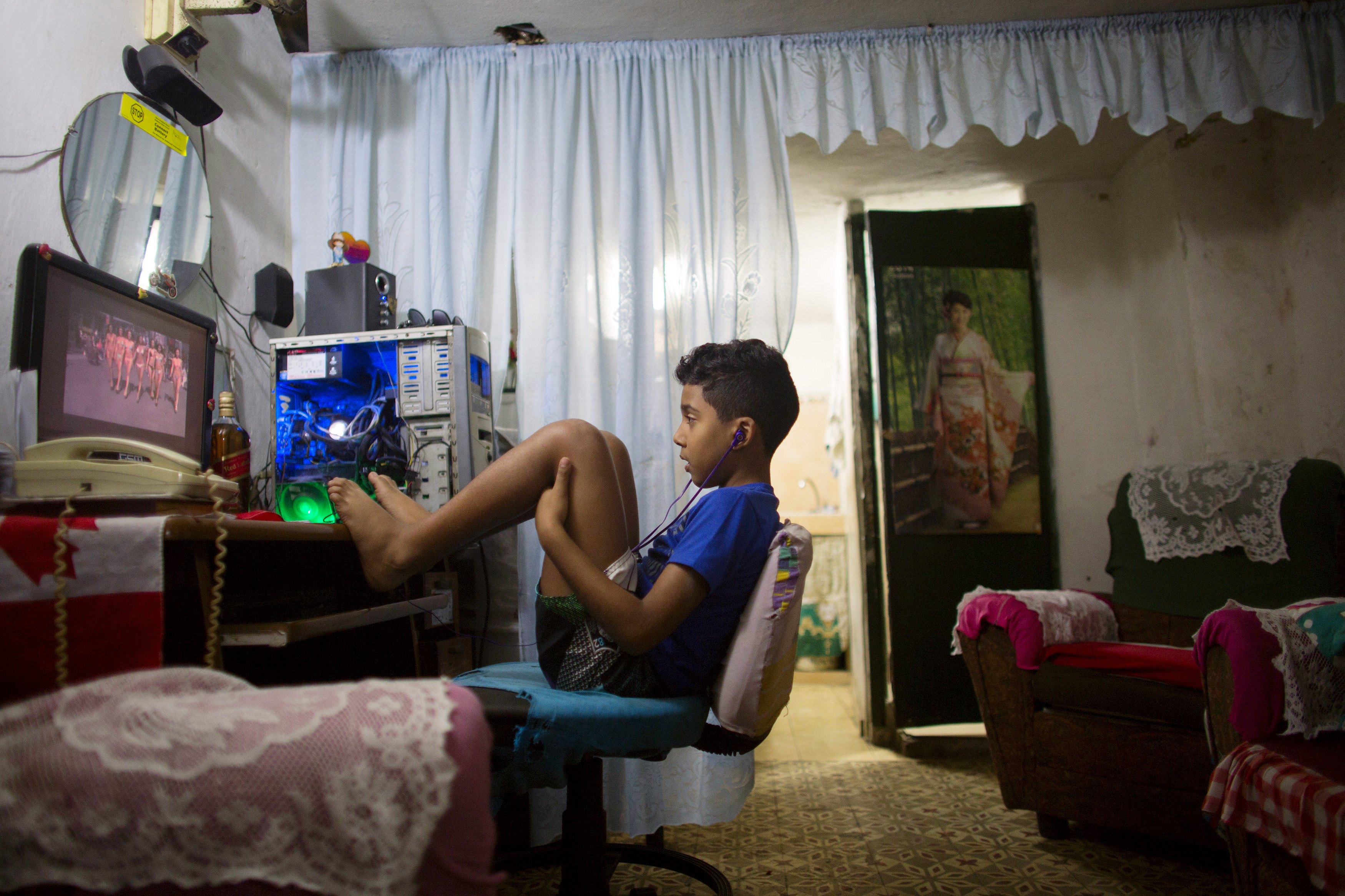 Havana resident Kevin Lachaise watches a recorded TV show on a computer screen in the living room of his home.