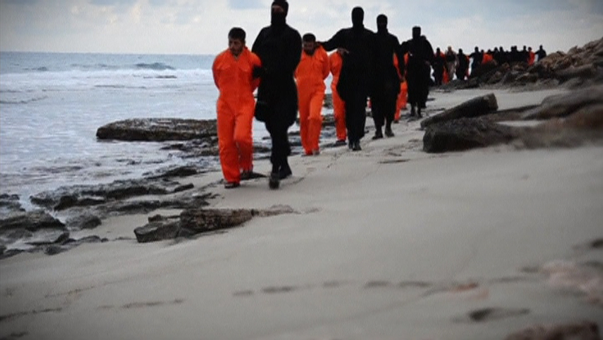 Men in orange jumpsuits purported to be Egyptian Christians held captive by the Islamic State (IS) are marched by armed men along a beach said to be near Tripoli, in this still image from an undated video made available on social media on February 15, 201
