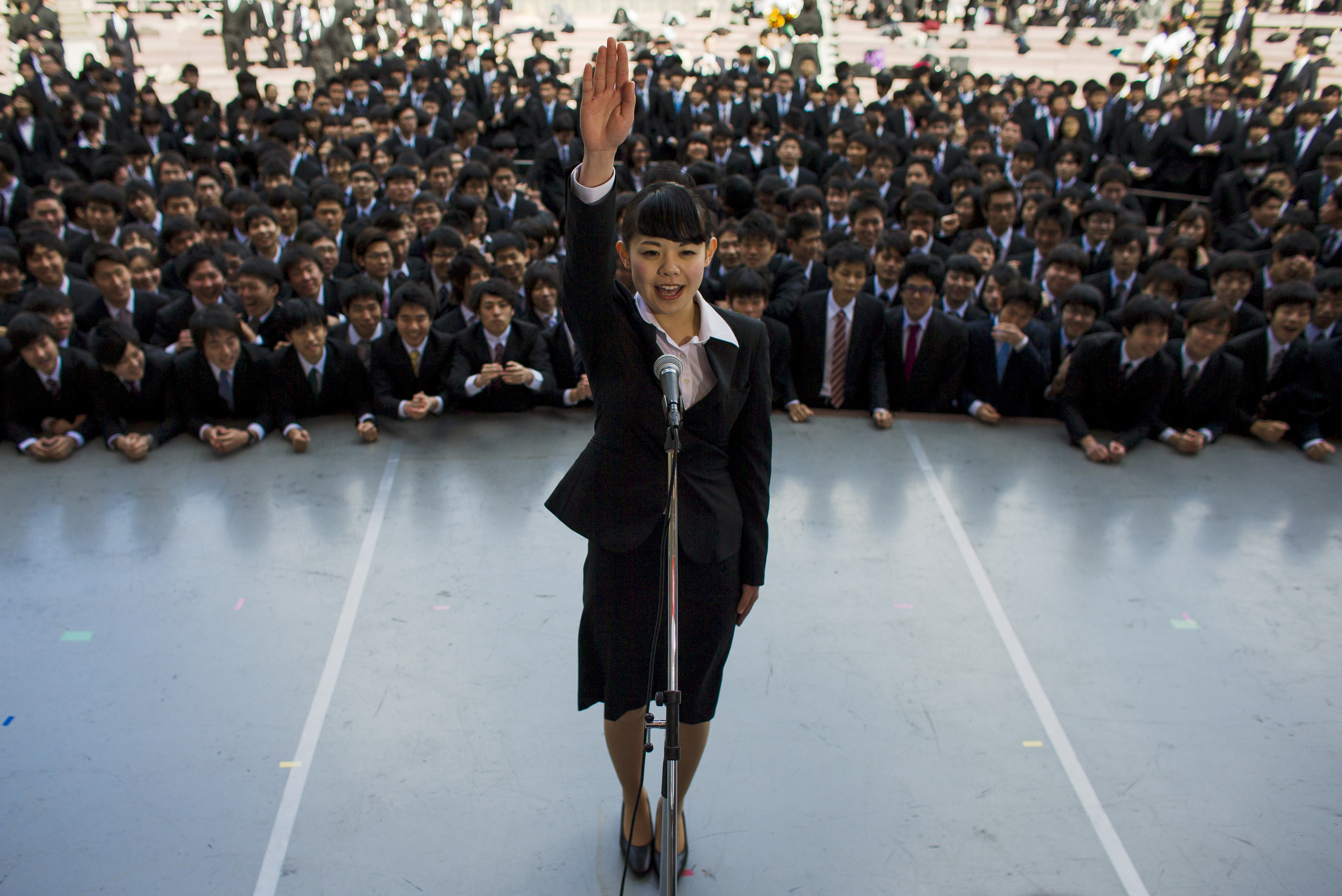 A Japanese college graduate publicly promises that she will do her best in trying to find work during a job-hunting rally at an outdoor theatre in Tokyo.