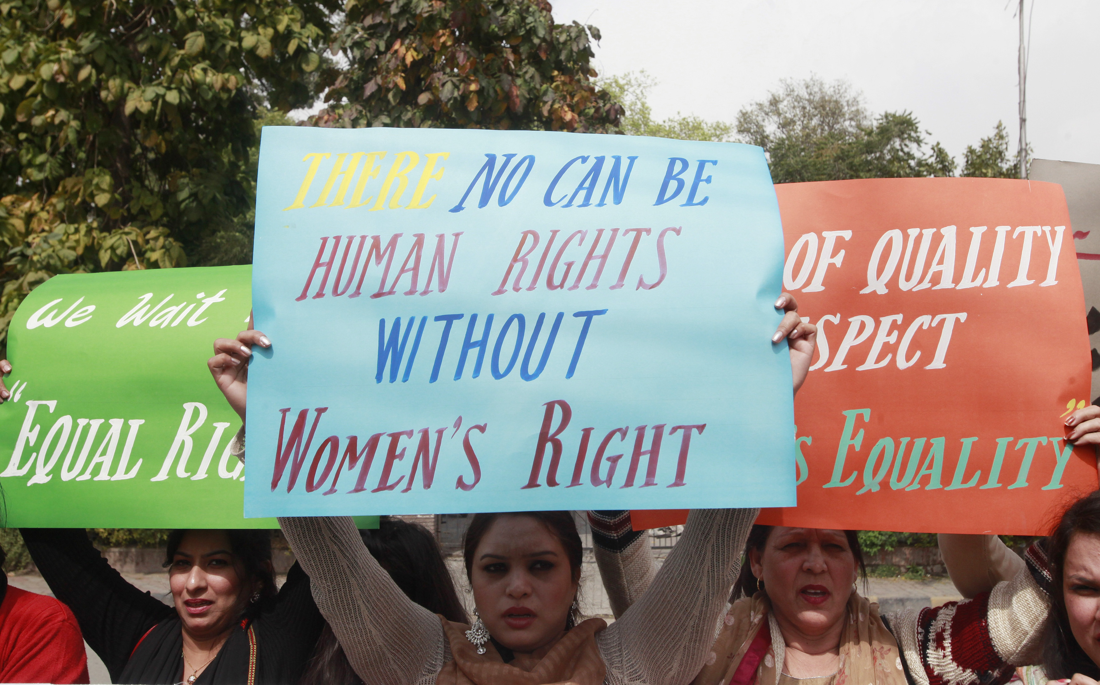 Women hold up signs during an International Women's Day rally in Lahore, March 8, 2015. Reuters/Mohsin Raza