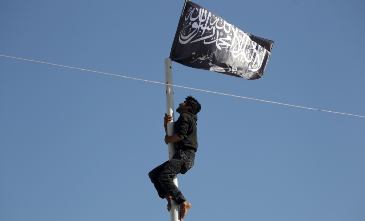 A member of the Nusra Front climbs a pole where the al-Qaeda-affiliate's flag was raised at a central square in the northwestern Syrian city of Ariha, in Idlib province, after a coalition of insurgent groups seized the area on May 29, 2015.