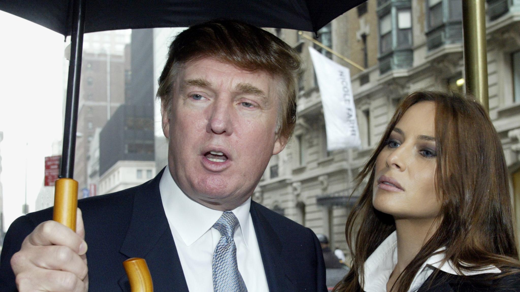Donald Trump and Melania Trump under an umbrella