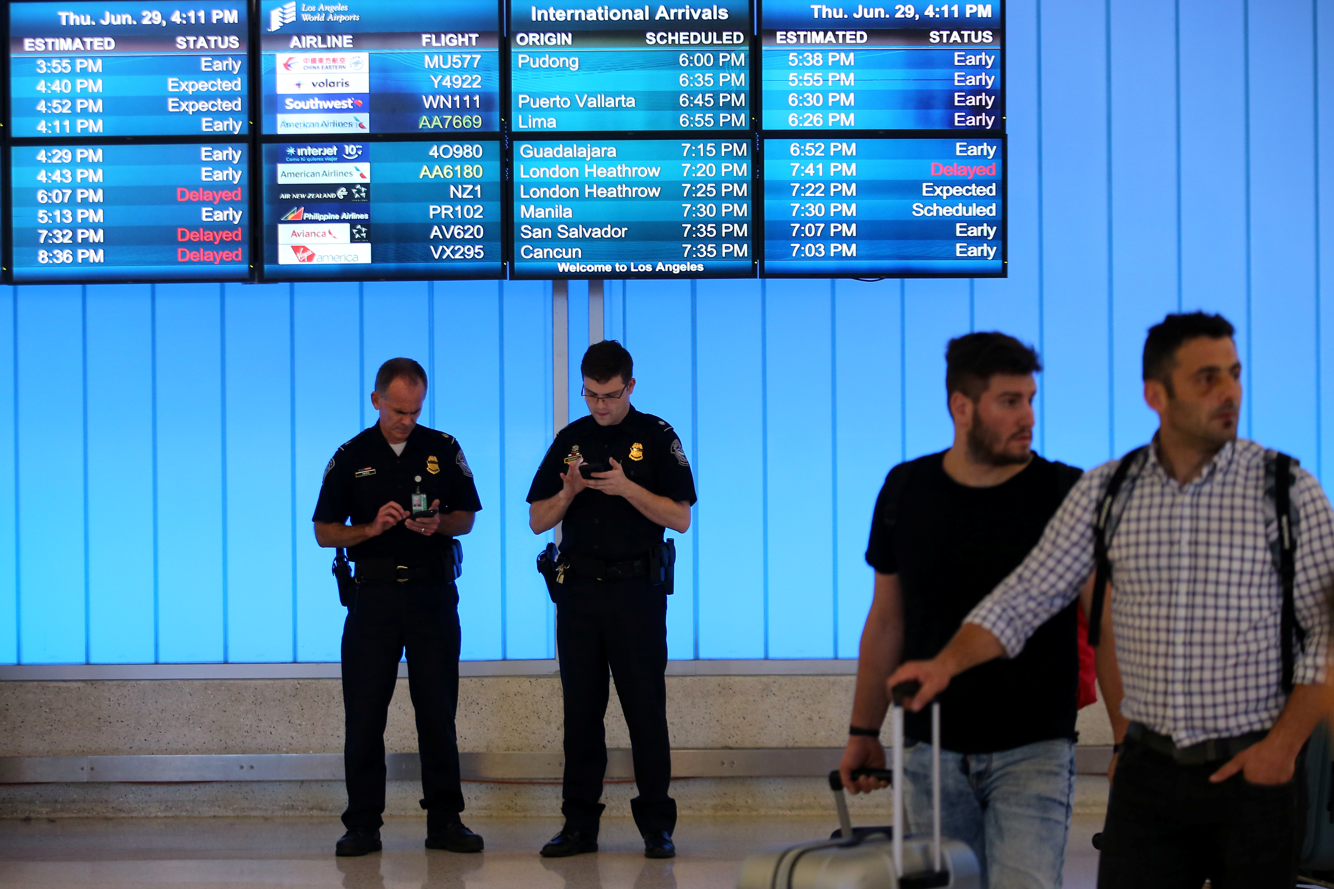 US Customs and Immigration officers keep watch at the arrivals level at Los Angeles International Airport, June 29, 2017