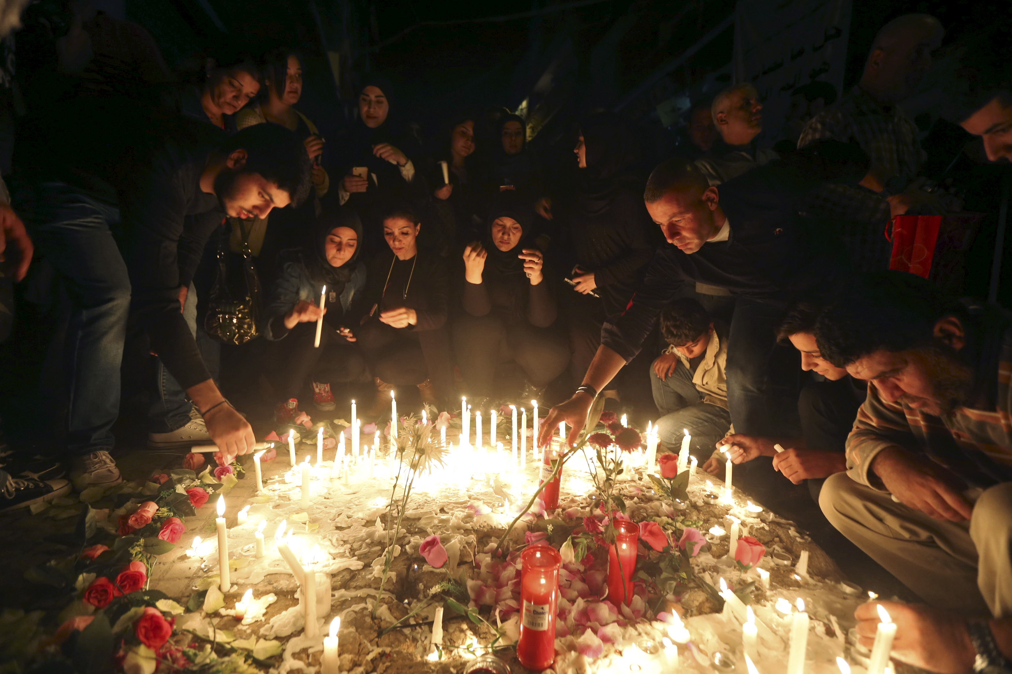 Beirut residents light candles during a vigil at the site of the two explosions that occurred on Thursday in the southern suburbs of the Lebanese capital Beirut,