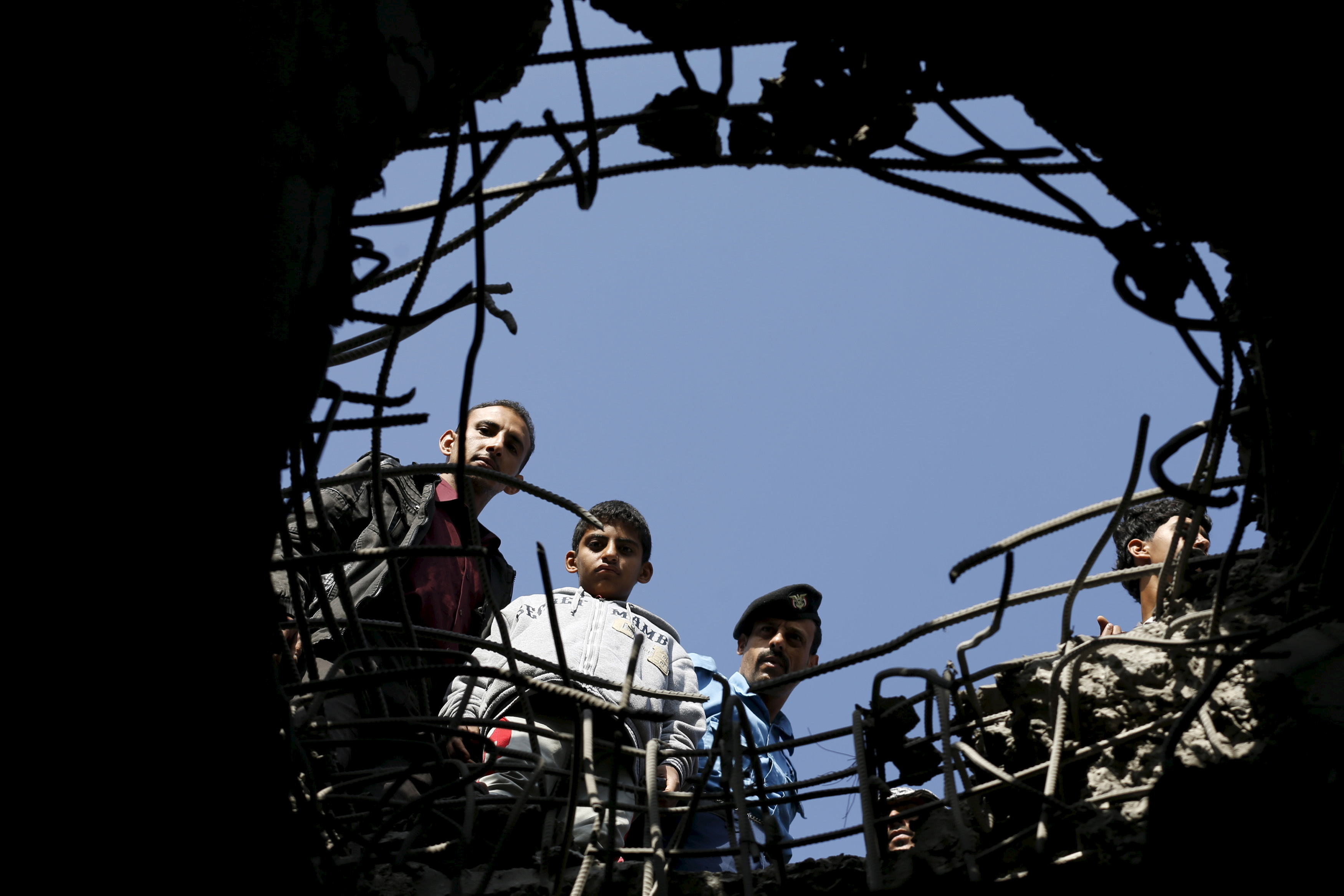 People look through a hole caused by a Saudi-led air strike