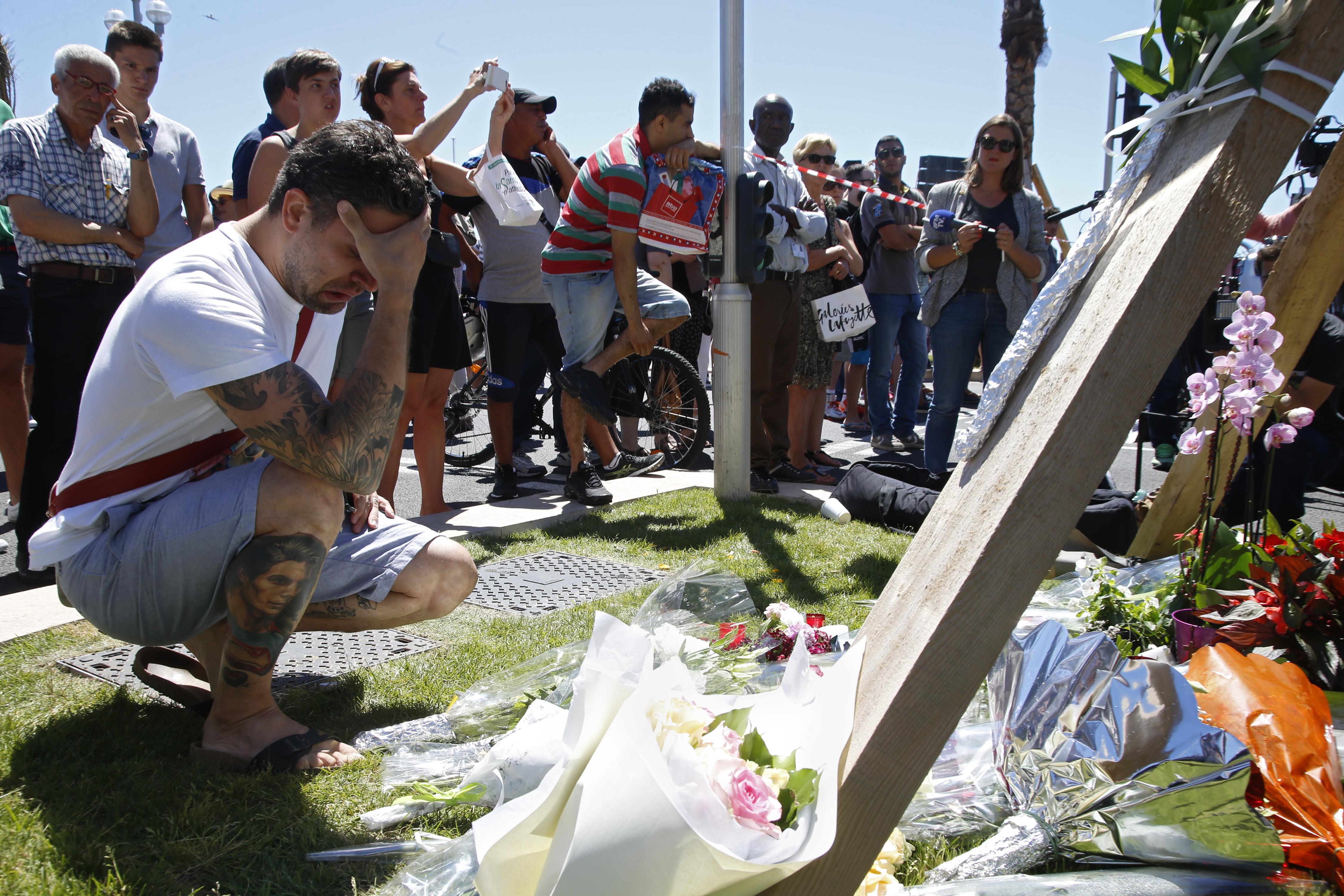Man kneels in front of make-shift memorial with head in hands