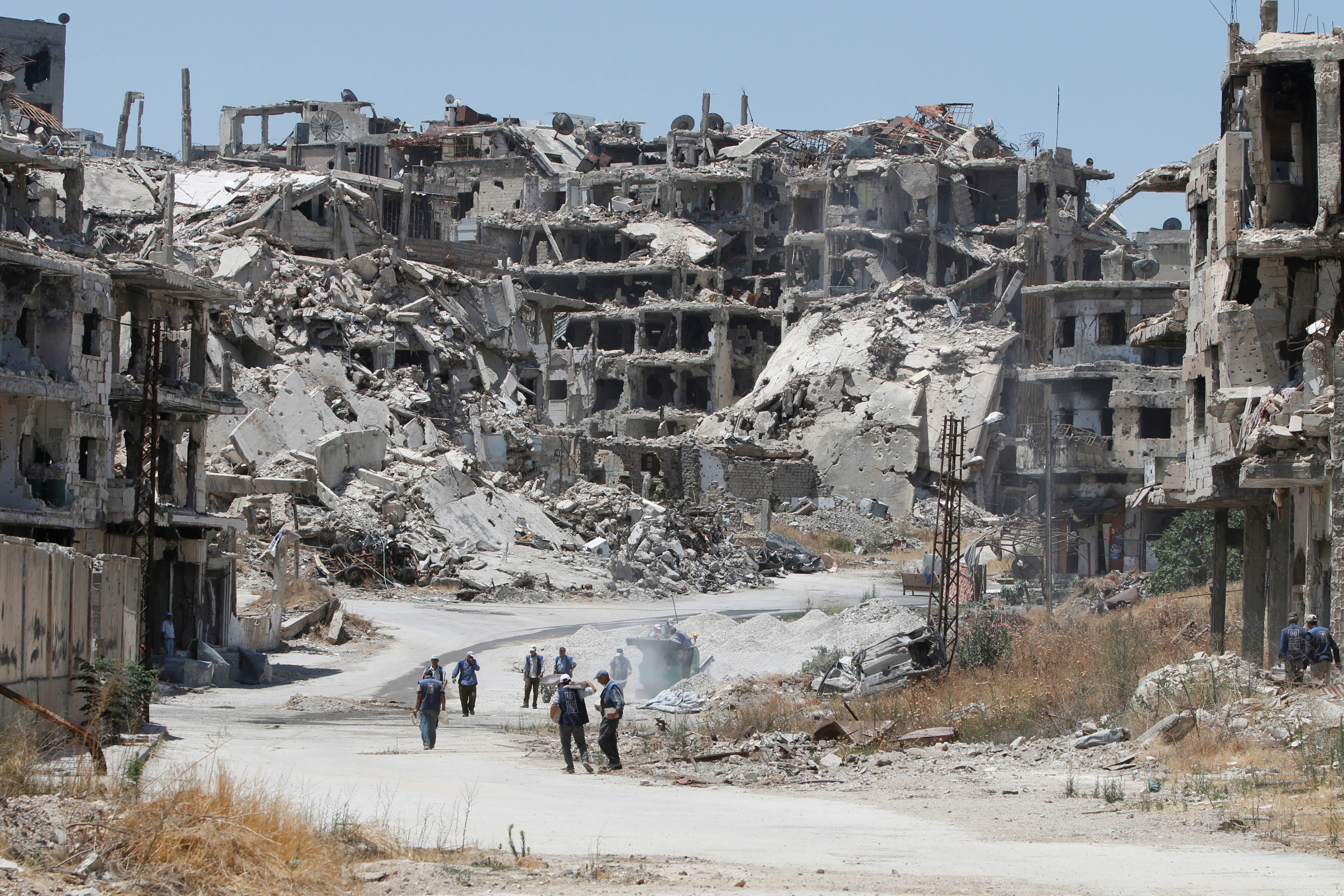 Workers collect material to be recycled and reused for reconstruction, under the supervision of the United Nations Development Programme in government-controlled Homs, Syria.