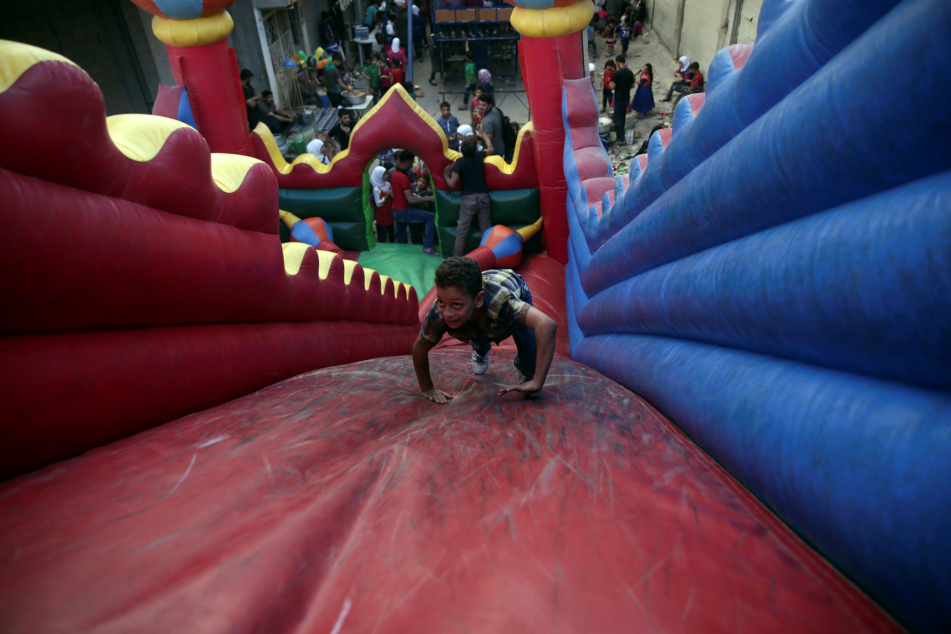 Children played on the bouncy castle on the last day of the Muslim holiday of Eid al-Adha in the rebel held besieged town of Hamouriyeh, outside of the Syrian capital of Damascus on Thursday, September 15, 2016.