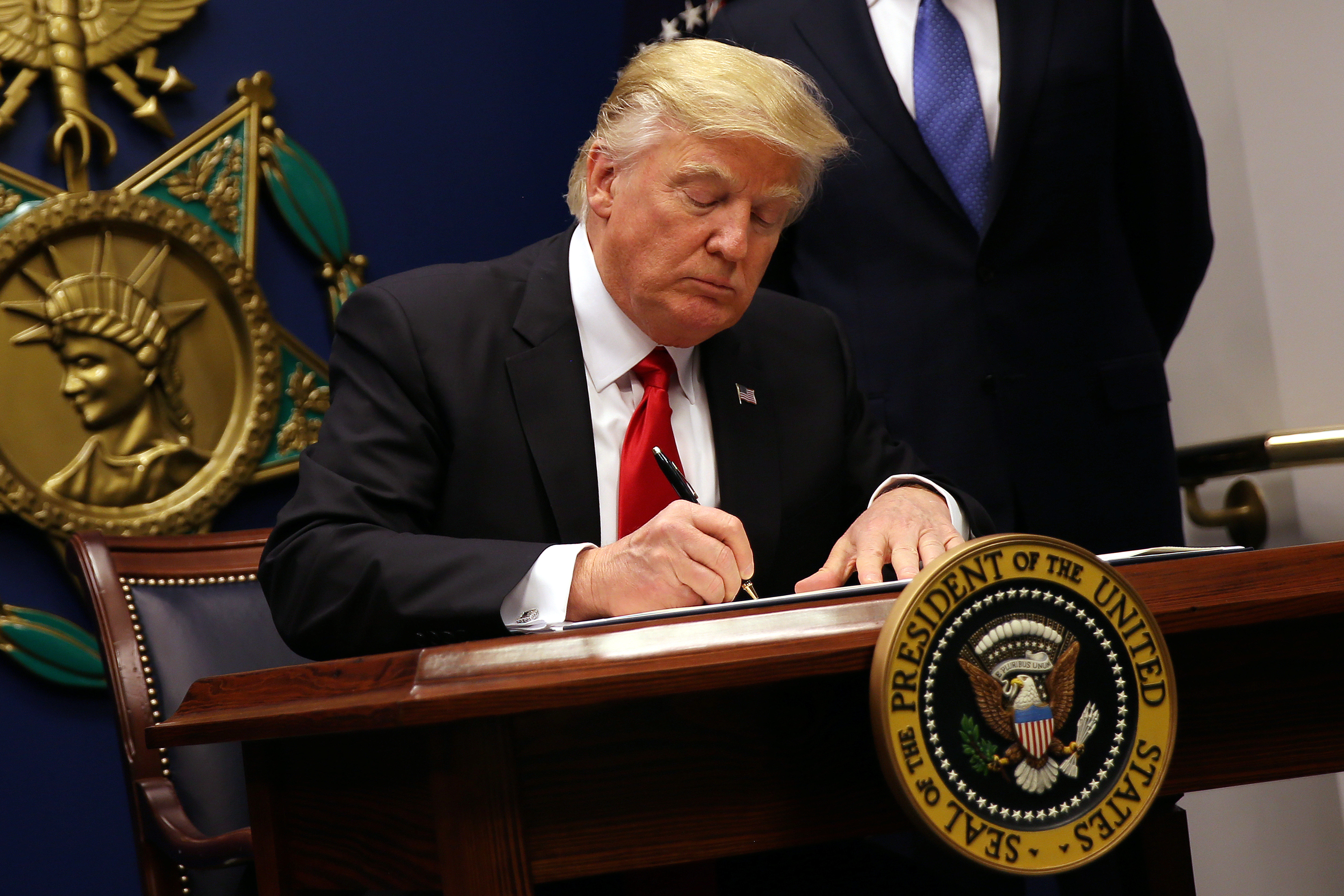 President Donald Trump signs an executive order to impose tighter vetting of travelers entering the United States, at the Pentagon in Washington, D.C.