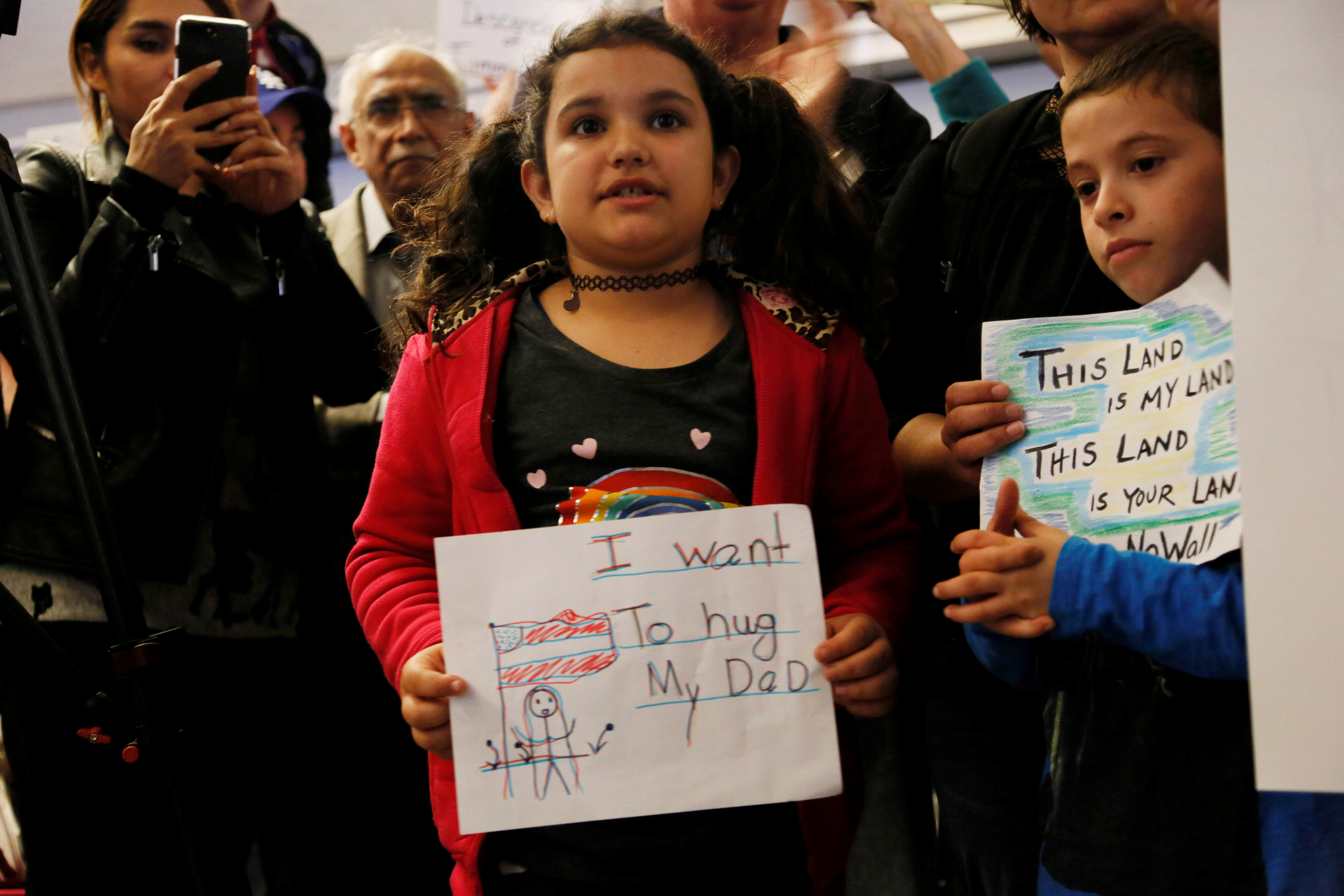 """Young girl holding sign in front of crowd, """"I want to hug my dad"""""""