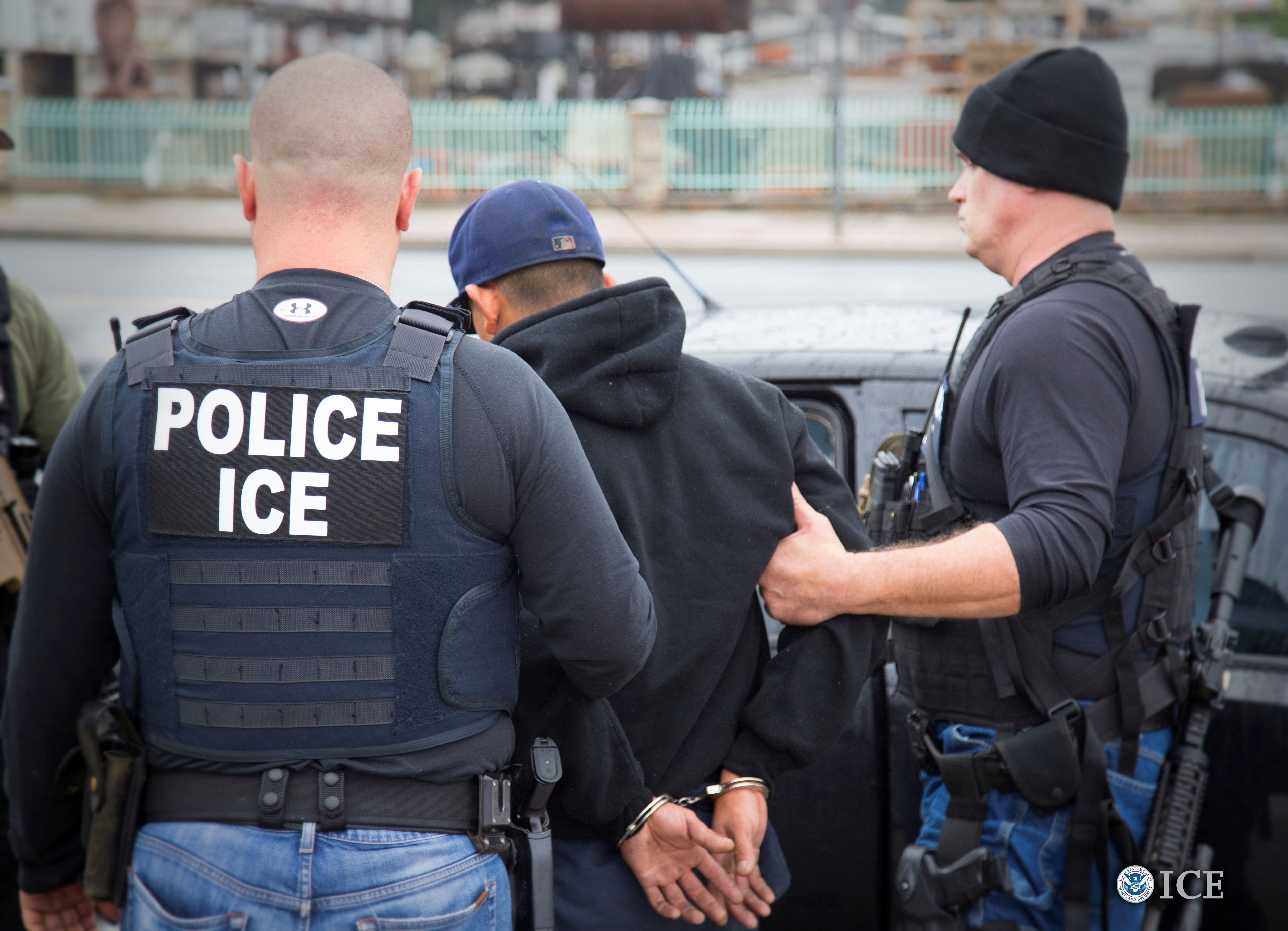 """Two men with vests that read """"POLICE ICE"""" lead away a man in handcuffs"""