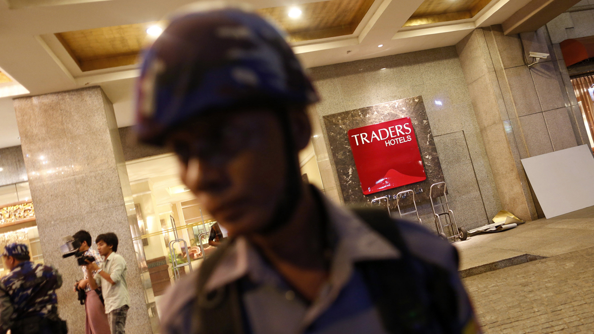 A police officer stands in front of Traders Hotel, where an explosion occurred, in central Yangon early October 15, 2013.