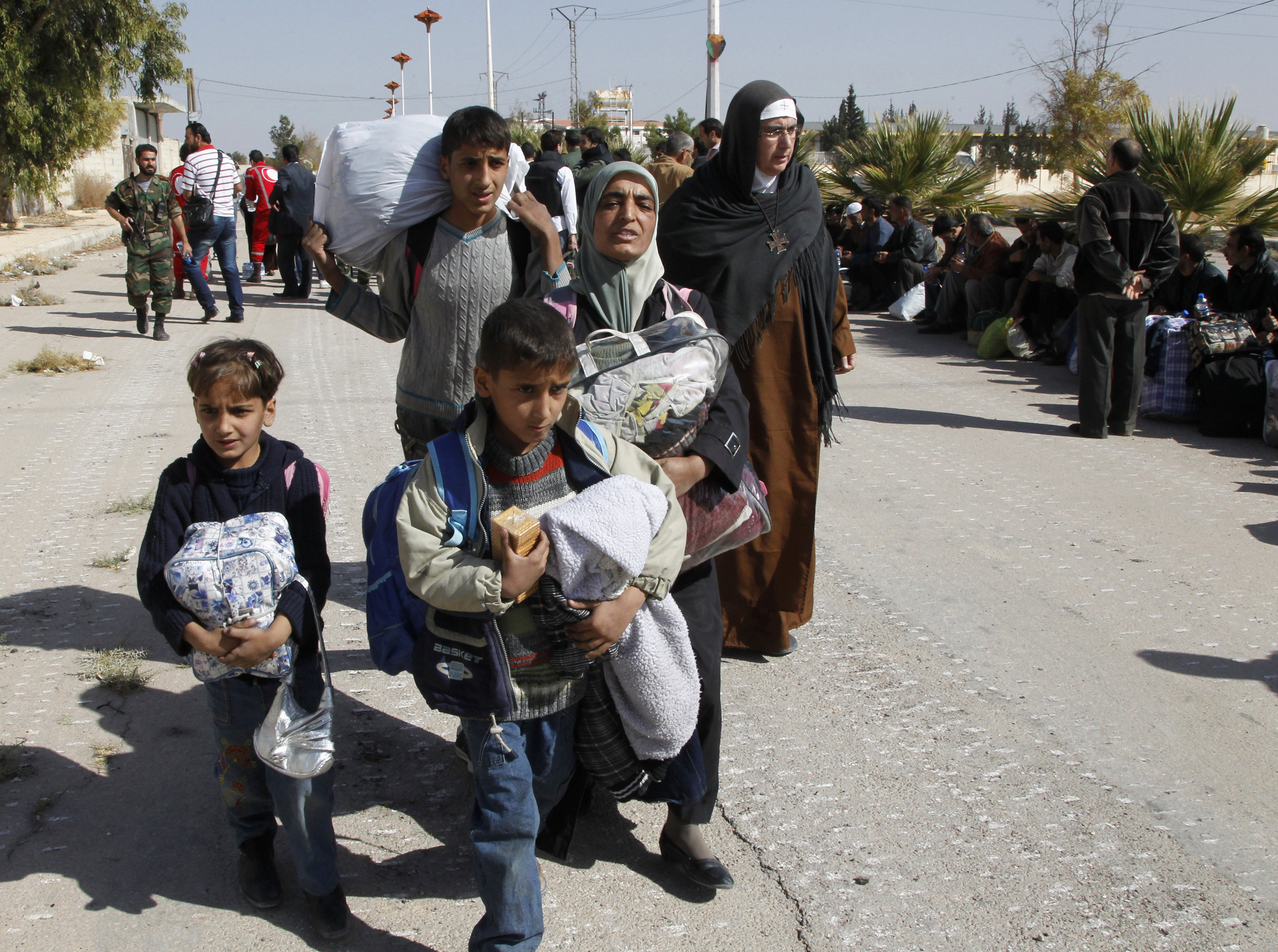 Syrian families were allowed to flee rebel-controlled Moadamiya Tuesday, in a rare instance of coordination between the Syrian government and the opposition.