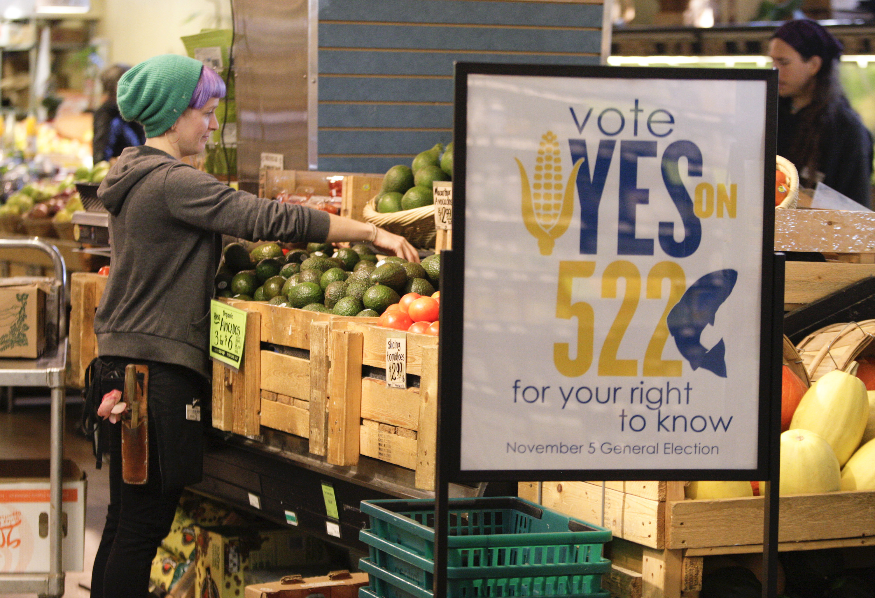 An employee at a Seattle co-op stocks produce near a sign supporting a 2013 ballot initiative in Washington state that would have required labeling of GMO foods. The initiative failed, with record amounts of money spent to defeat it.