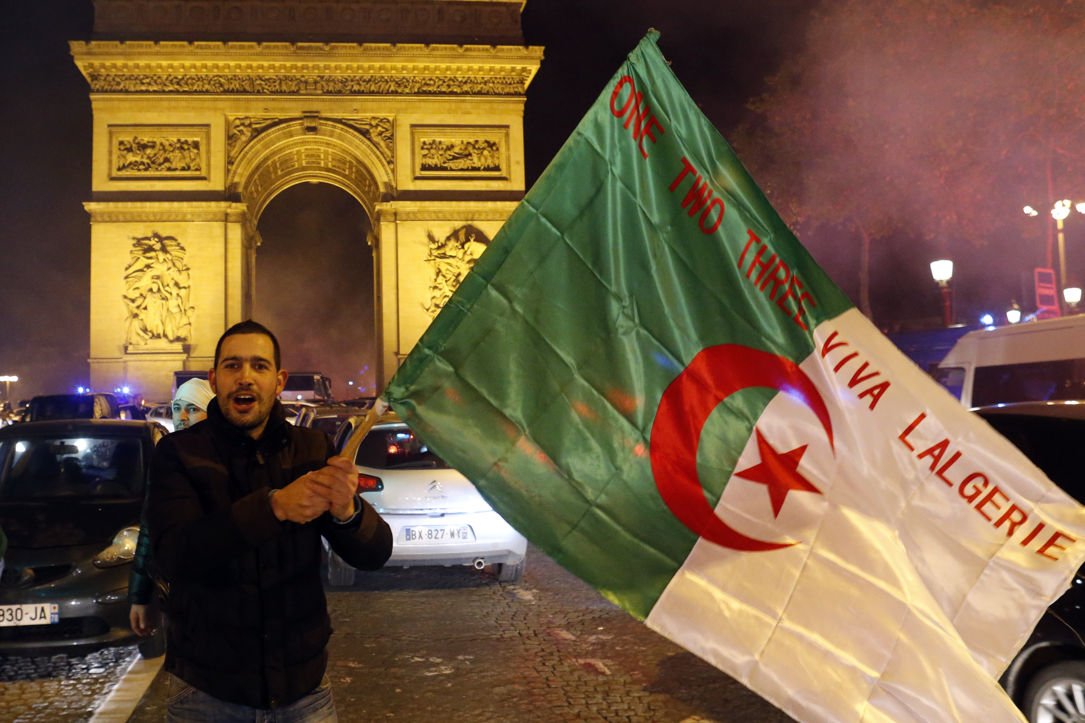 An Algerian soccer fan waves the Algerian flag in front of the Arc de Triomphe in Paris. With 16 French-born players on the Algerian team, Franco-Algerians have celebrated the Algerian victories with huge celebrations in French cities.