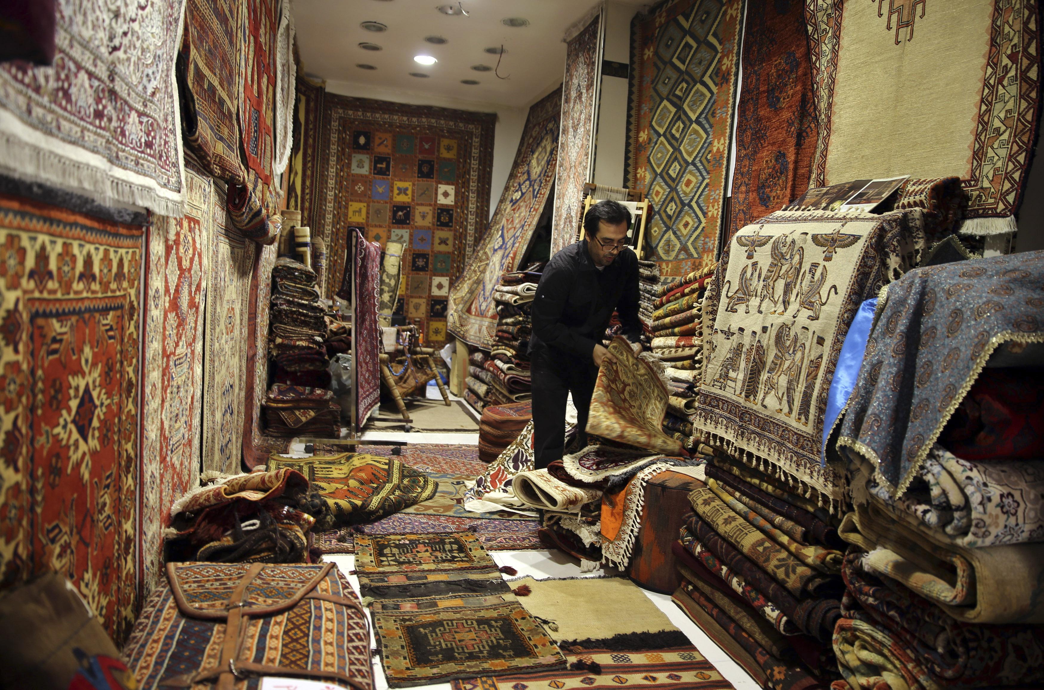 A seller arranges Iranian carpets at his shop in Dubai old market November 24, 2013.