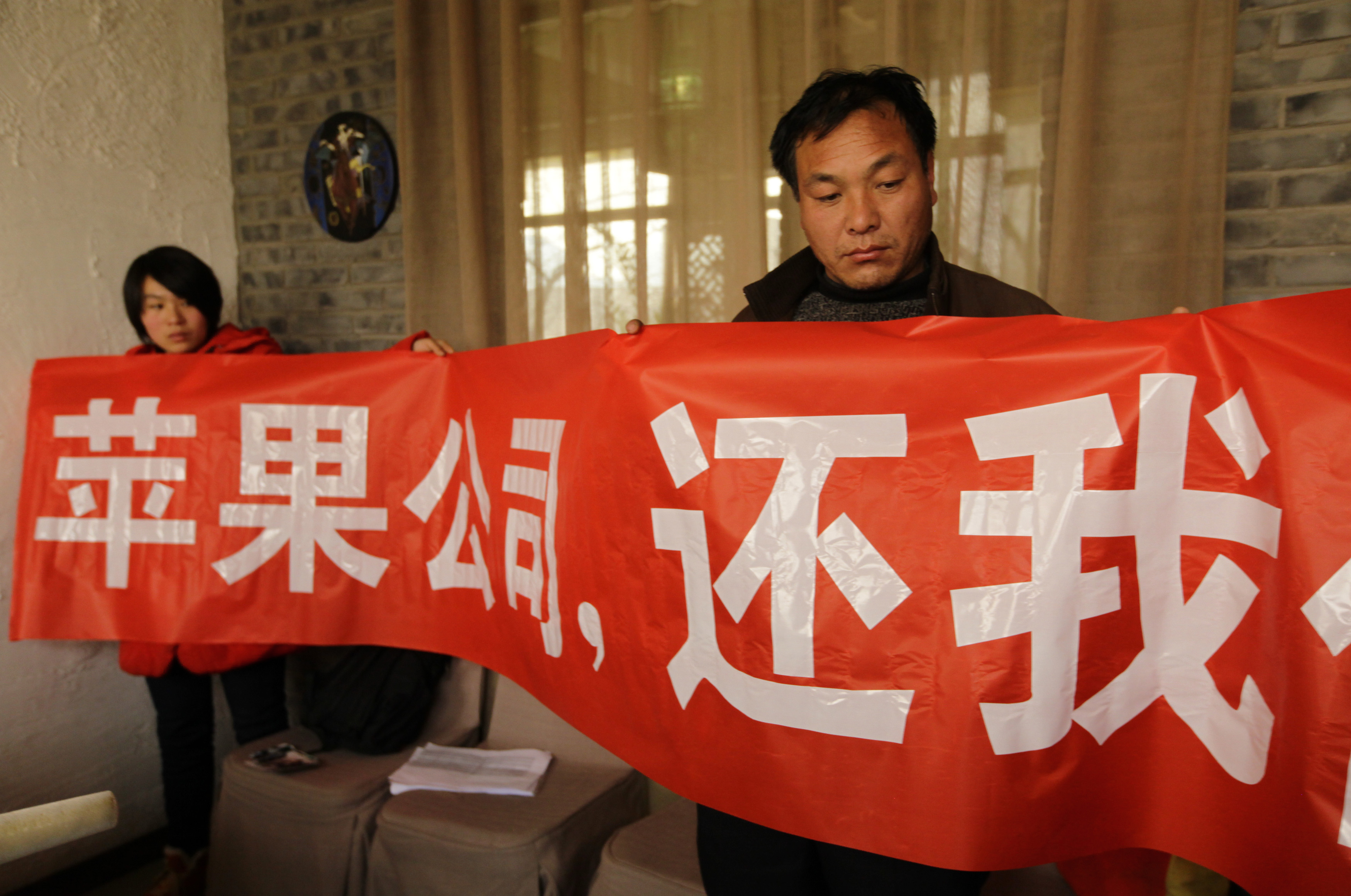 Shi Zengqiang, on the right, the father of a 15-year-old worker at Chinese manufacturing company Pegatron worker who died of pneumonia, holds a banner at a news conference in Beijing on December 16, 2013.