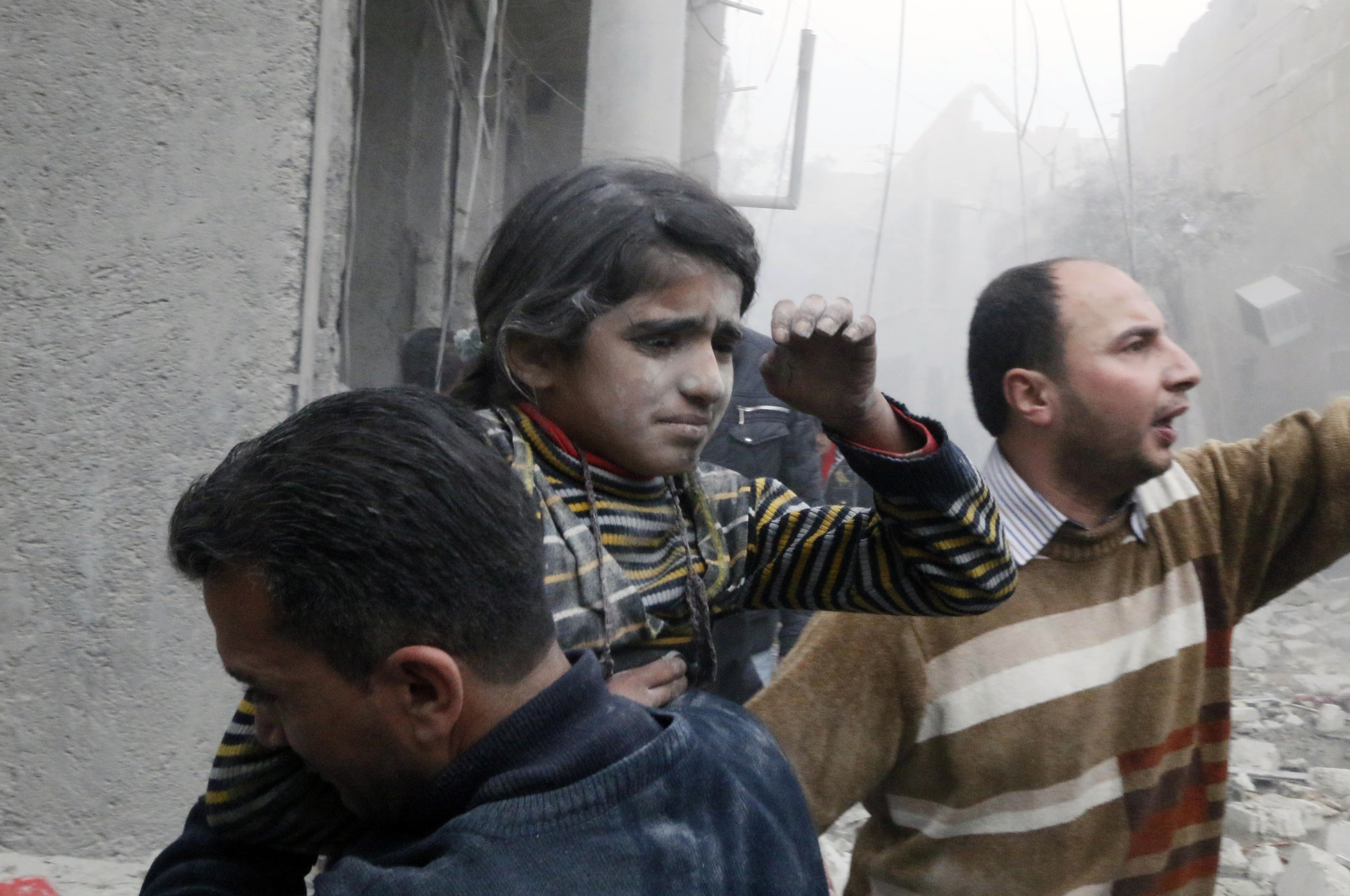 A Syrian girl is rescued from a damaged building after both of her parents died in what activists said was a government air strike.
