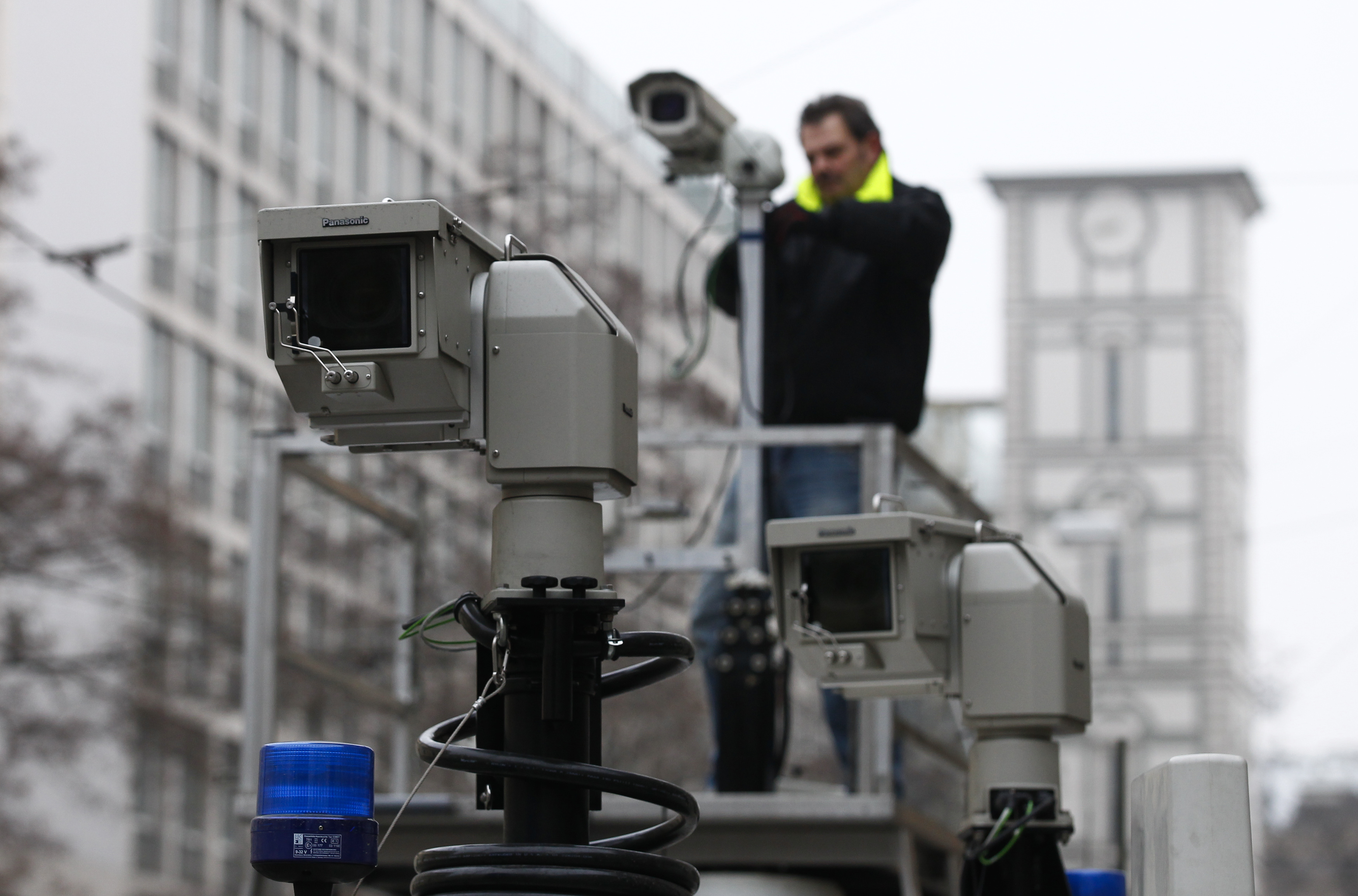 A man assembles police observation cameras near the Bayerischer Hof hotel before the start of the 50th Conference on Security Policy in Munich on January 31, 2014