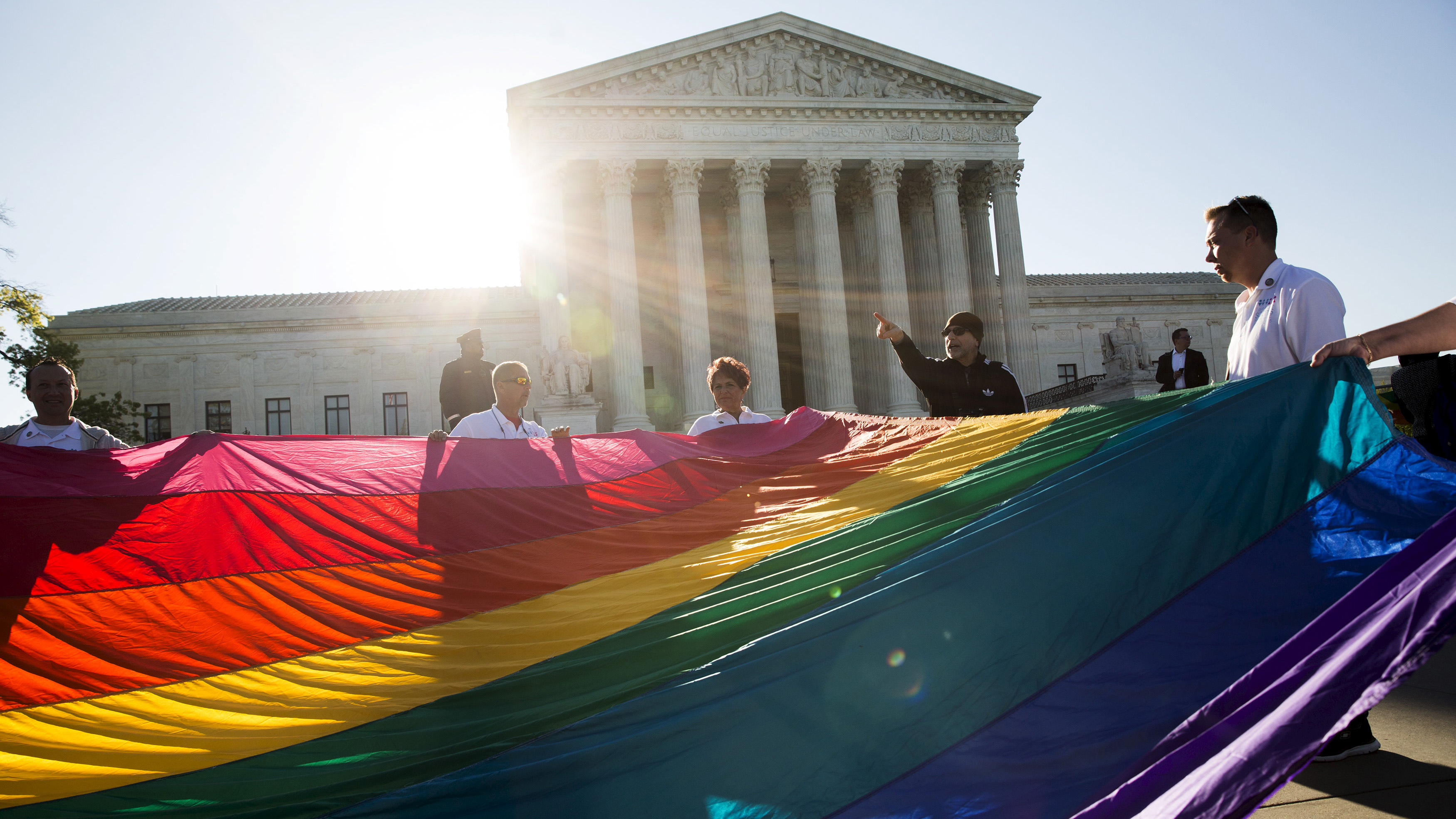 Gay marriage supporters hold a gay rights flag in front of the Supreme Court before a hearing about gay marriage on April 28, 2015.
