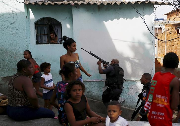 Residents observe as policemen take up position near an area where two men were found dead on top of the Sao Carlos slums complex in Rio de Janeiro May 15, 2015.