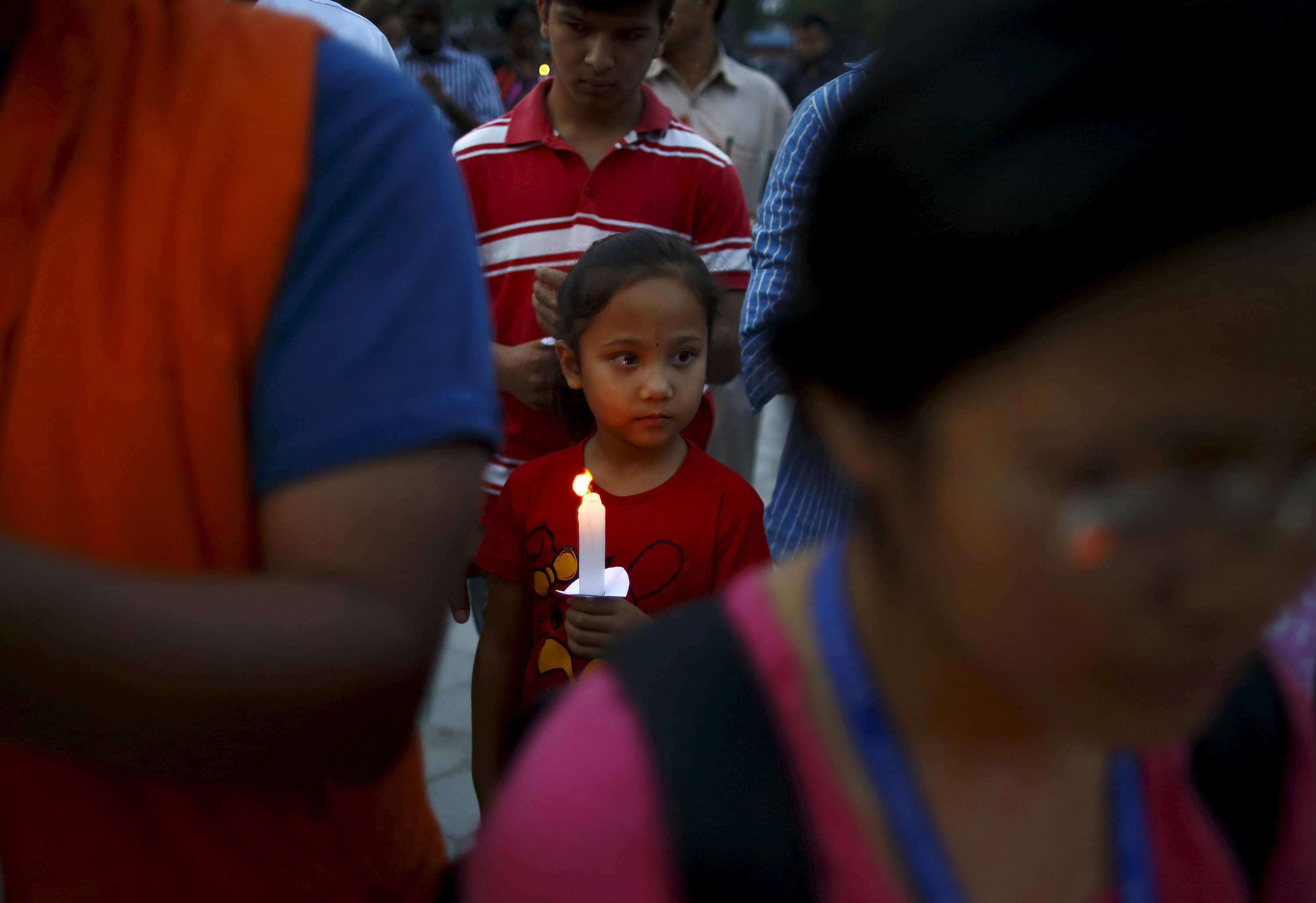 A girl holding a candle takes part in a candlelight vigil, a month after the April 25 earthquake, in Kathmandu, Nepal May 25, 2015.
