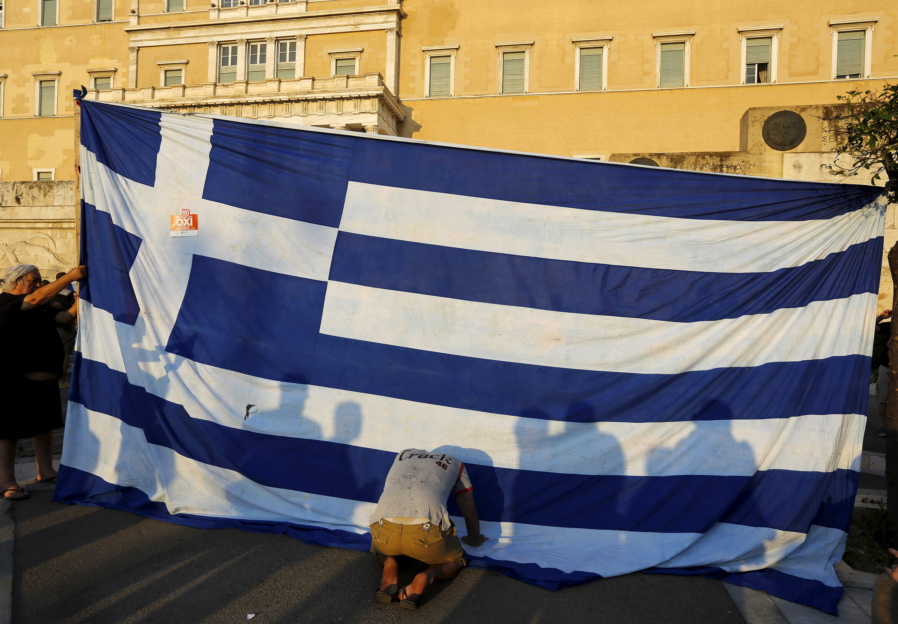 Protester kneels before Greek flag at protest in Athens