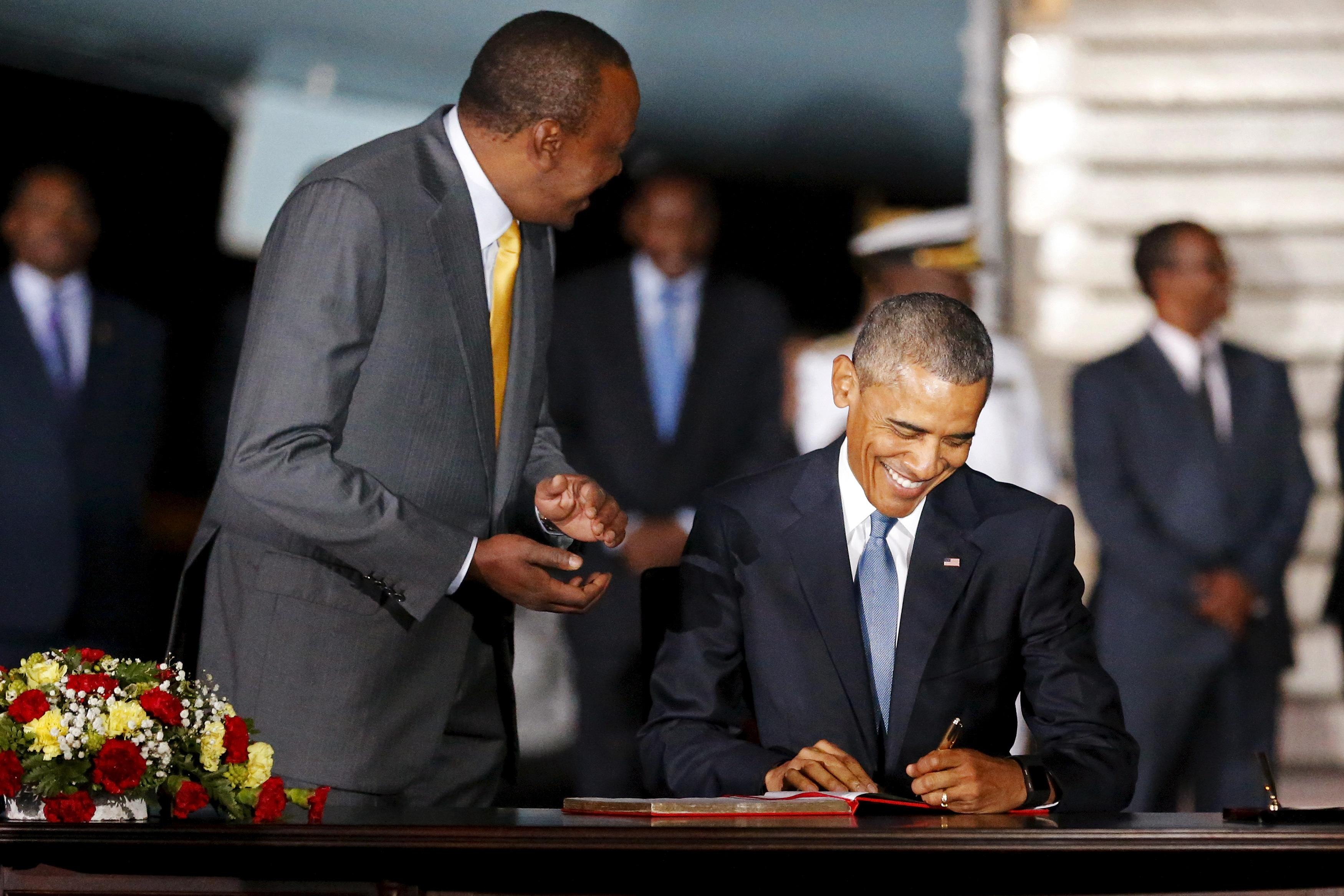 Kenya's President Uhuru Kenyatta (L) looks on as U.S. President Barack Obama signs a guest book as he arrives aboard Air Force One at Jomo Kenyatta International Airport in Nairobi July 24, 2015.