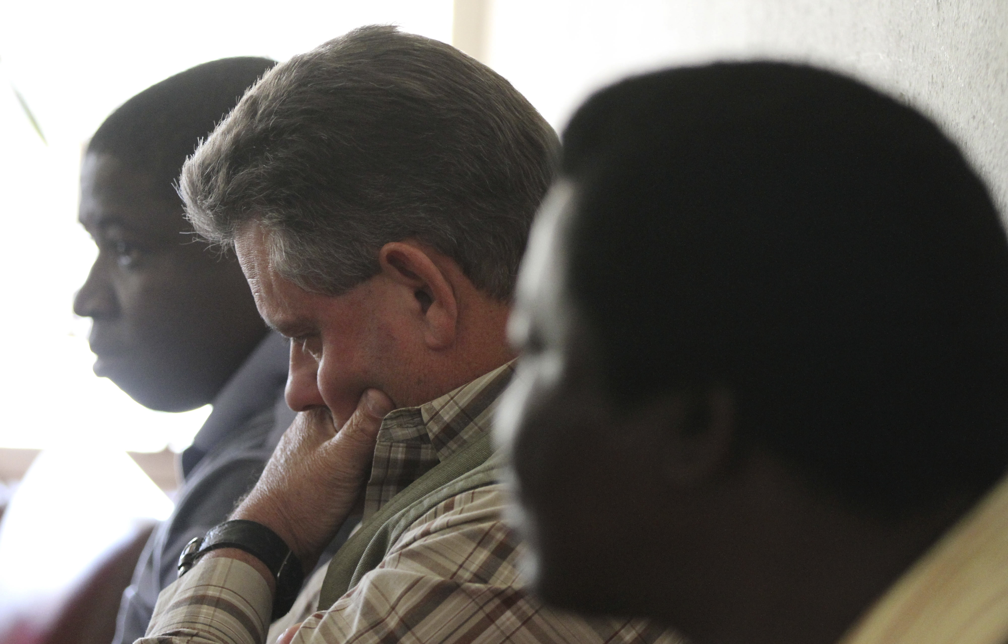 """Zimbabwean hunter Theo Bronkhorst (center) waits to appear in Hwange magistrates court. Bronkhorst is one of the two Zimbabwean men who were paid $50,000 by an American hunter who killed """"Cecil,"""" the country's best-known lion."""