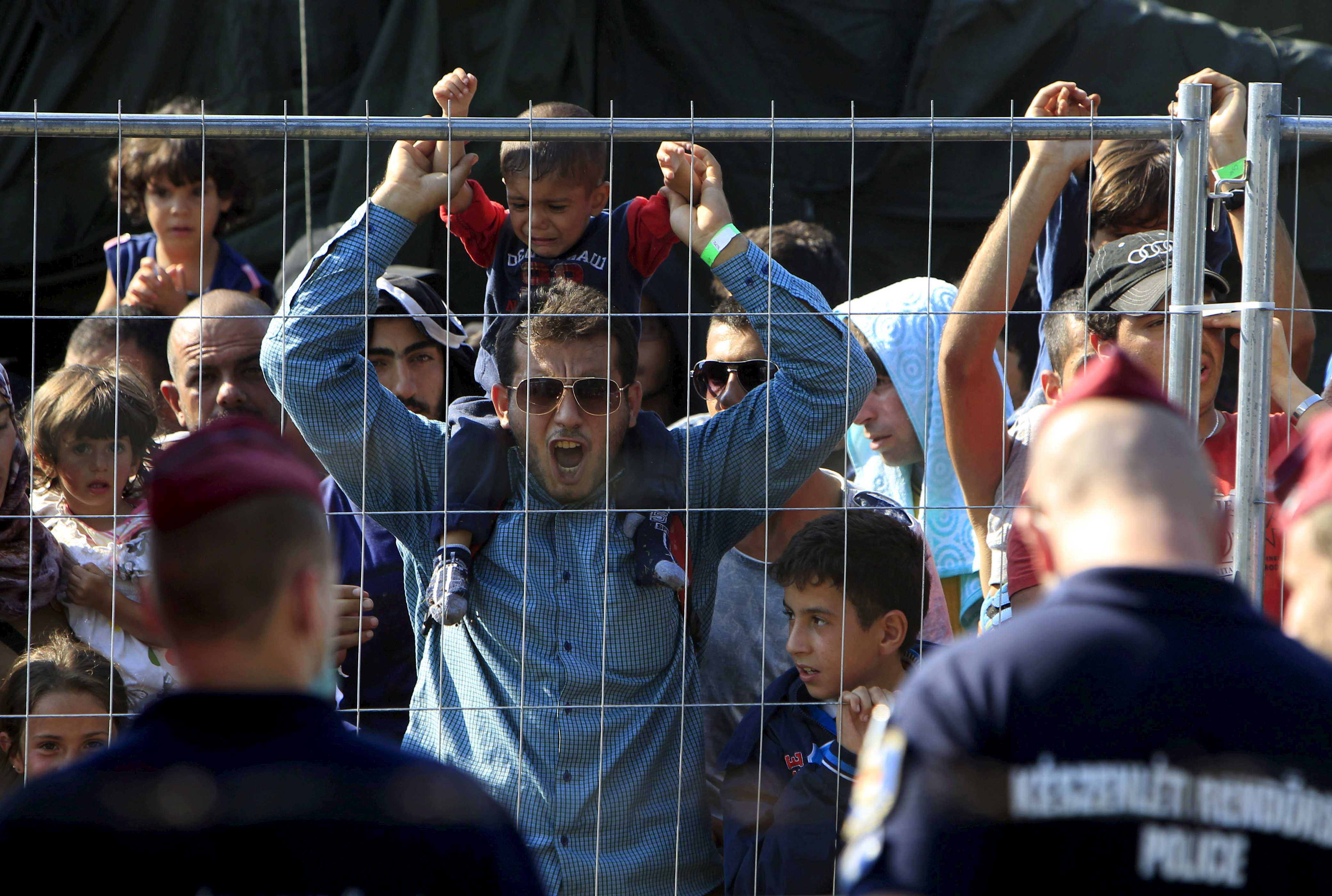 Syrian migrants shout slogans at a refugee camp in Roszke, Hungary, August 28, 2015.