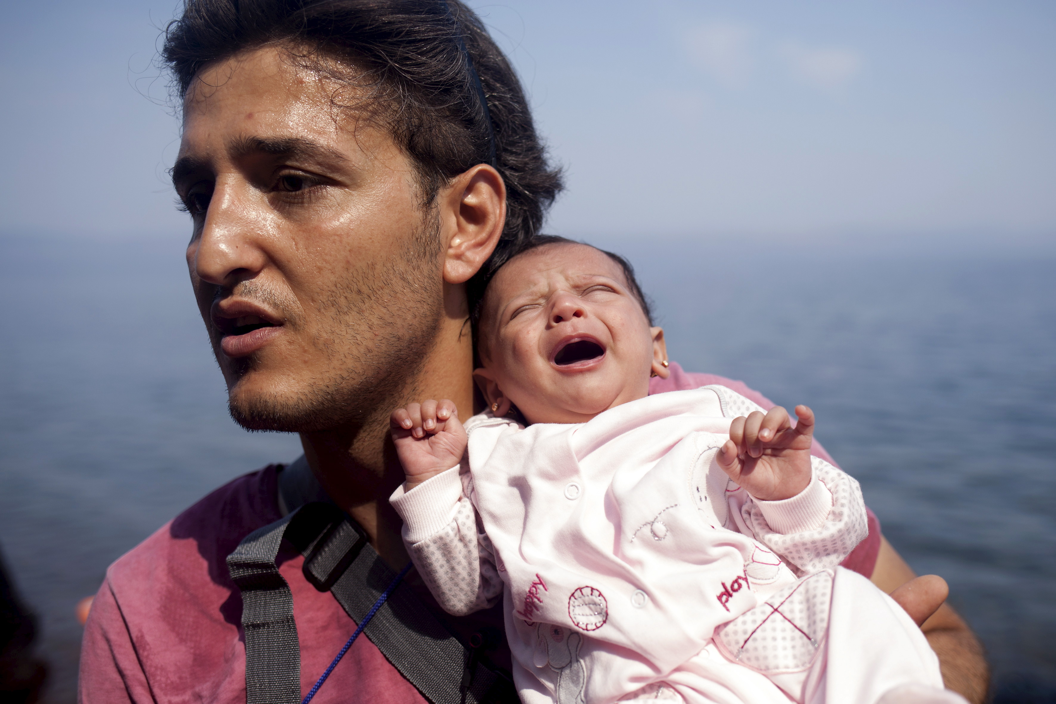 A Syrian refugee from Aleppo holds his one month old daughter moments after arriving on a dinghy on the Greek island of Lesbos