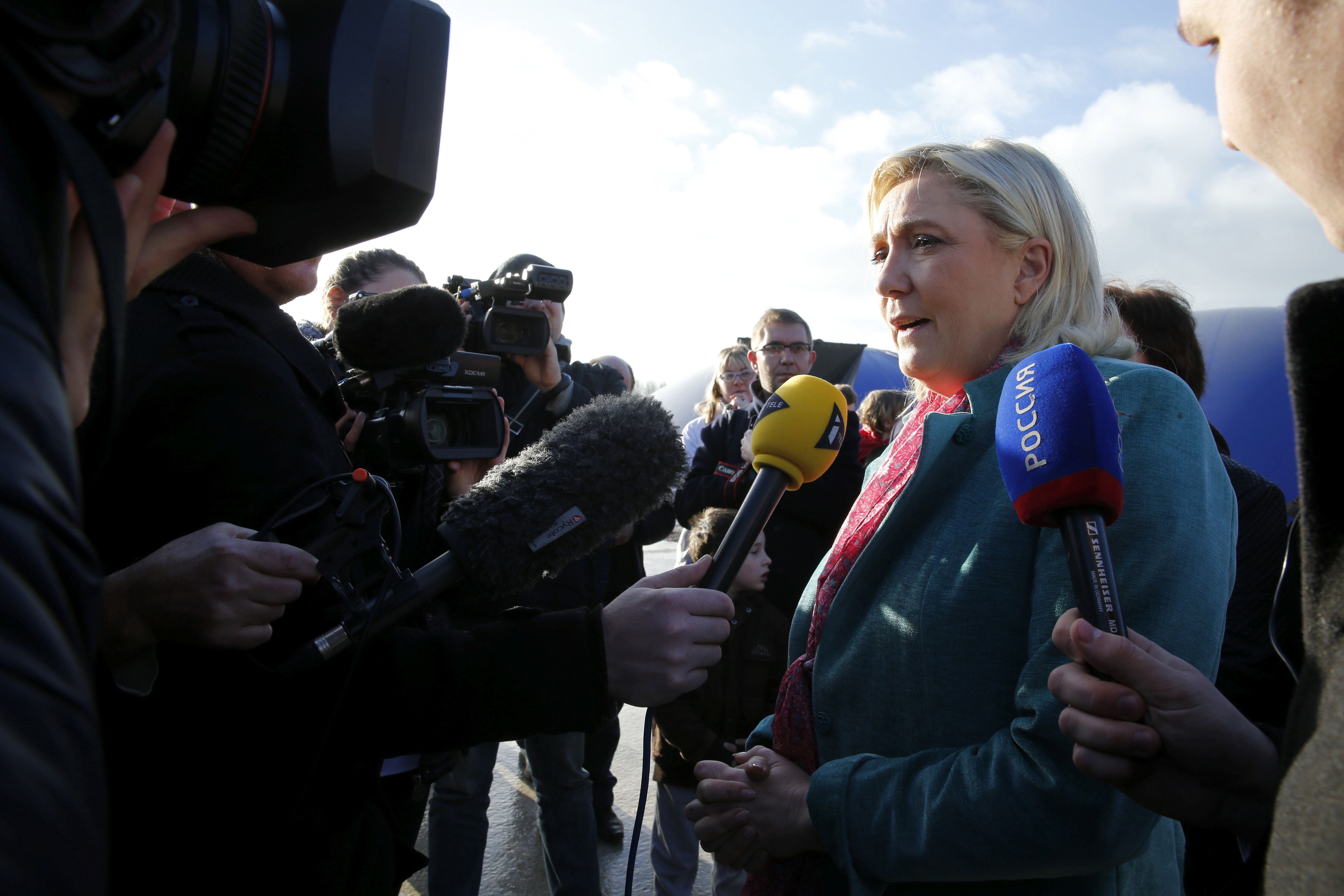 Marine Le Pen, French National Front political party leader and candidate for the National Front in the Nord-Pas-de-Calais-Picardie region, is surrounded by media as she campaigns for the upcoming regional elections