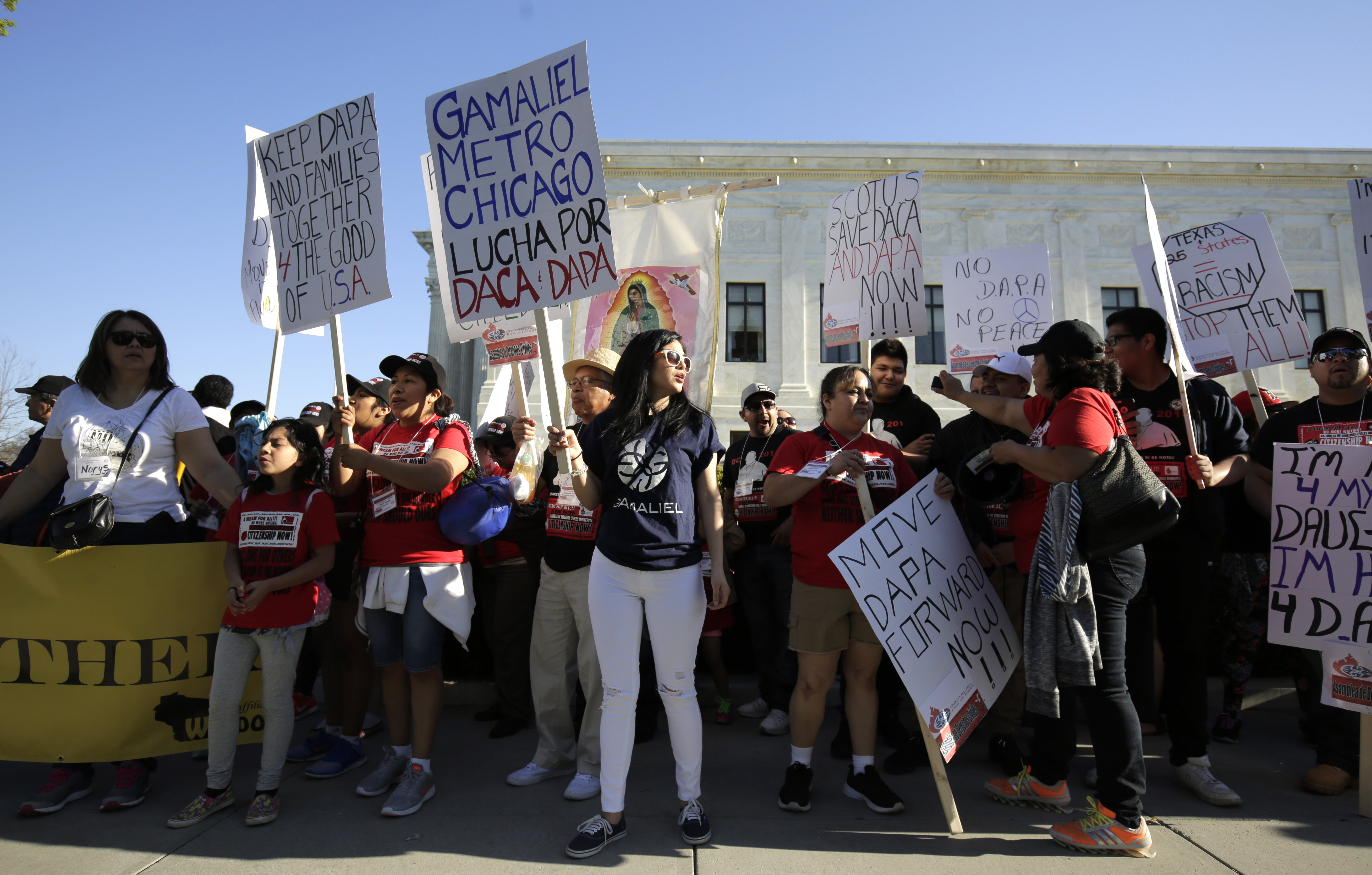Demonstrators hold signs asking the Supreme Court to allow DAPA to move forward