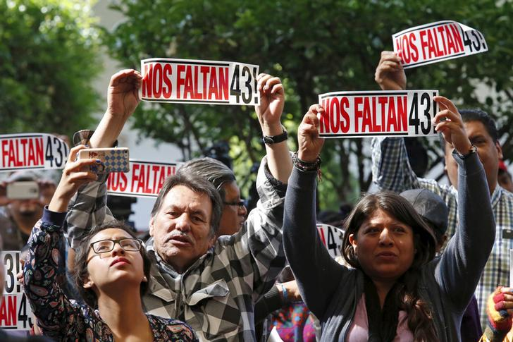 """Activists hold a sign that reads """"We are missing 43"""" during the delivery of the final report of the 43 missing students from the Ayotzinapa teacher's training college by members of the Inter-American Commission on Human Rights."""