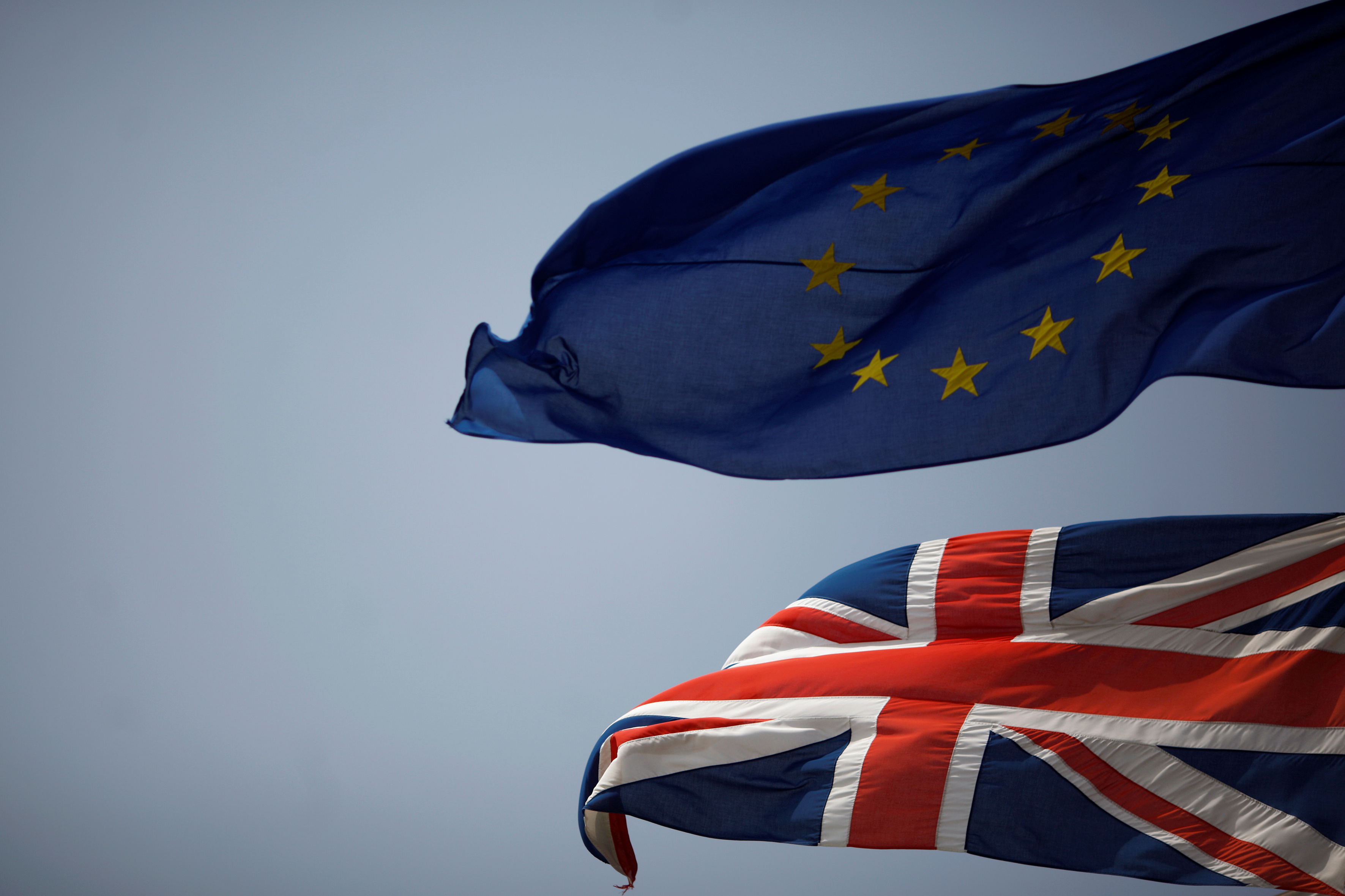 The Union Jack (bottom) and the European Union flag are seen flying, June 27, 2016, after Britain voted to leave the European Union in the EU Brexit referendum.