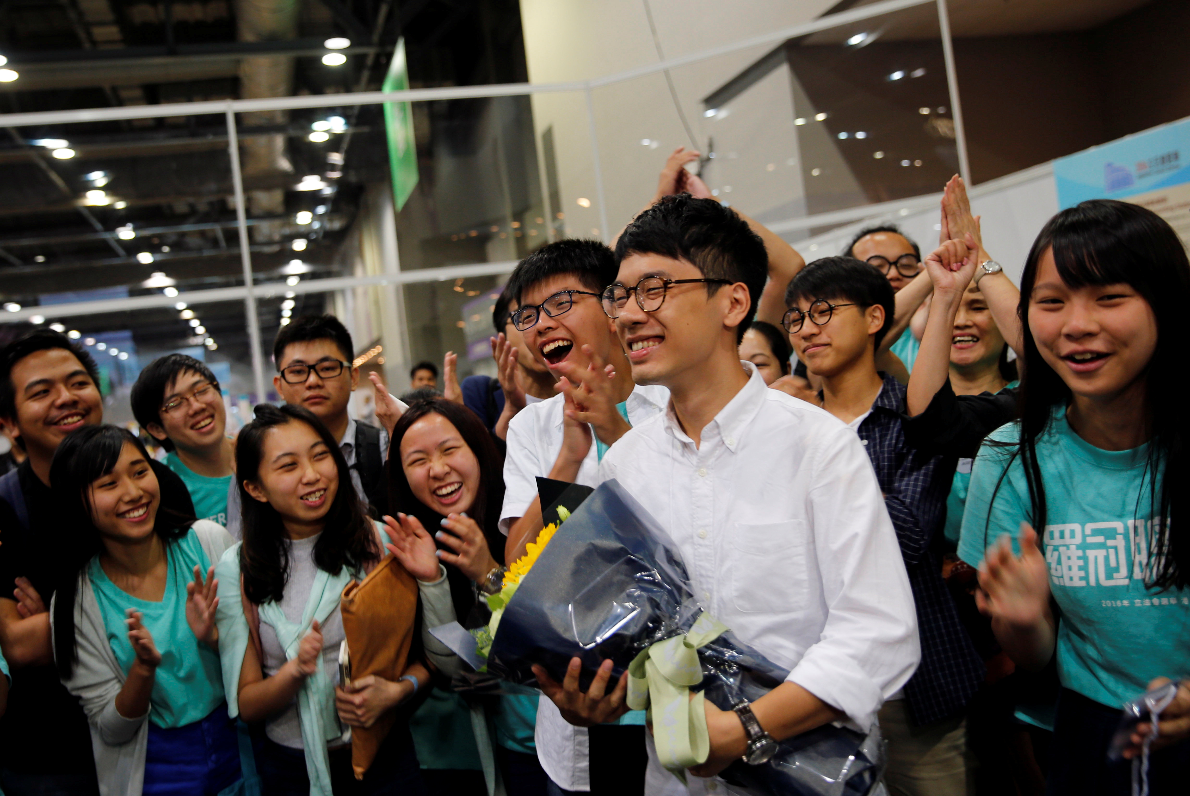 Student leader Joshua Wong (C) greets candidate Nathan Law (2nd R) as supporters share their joy after Law won in the Legislative Council election in Hong Kong, China September 5, 2016.