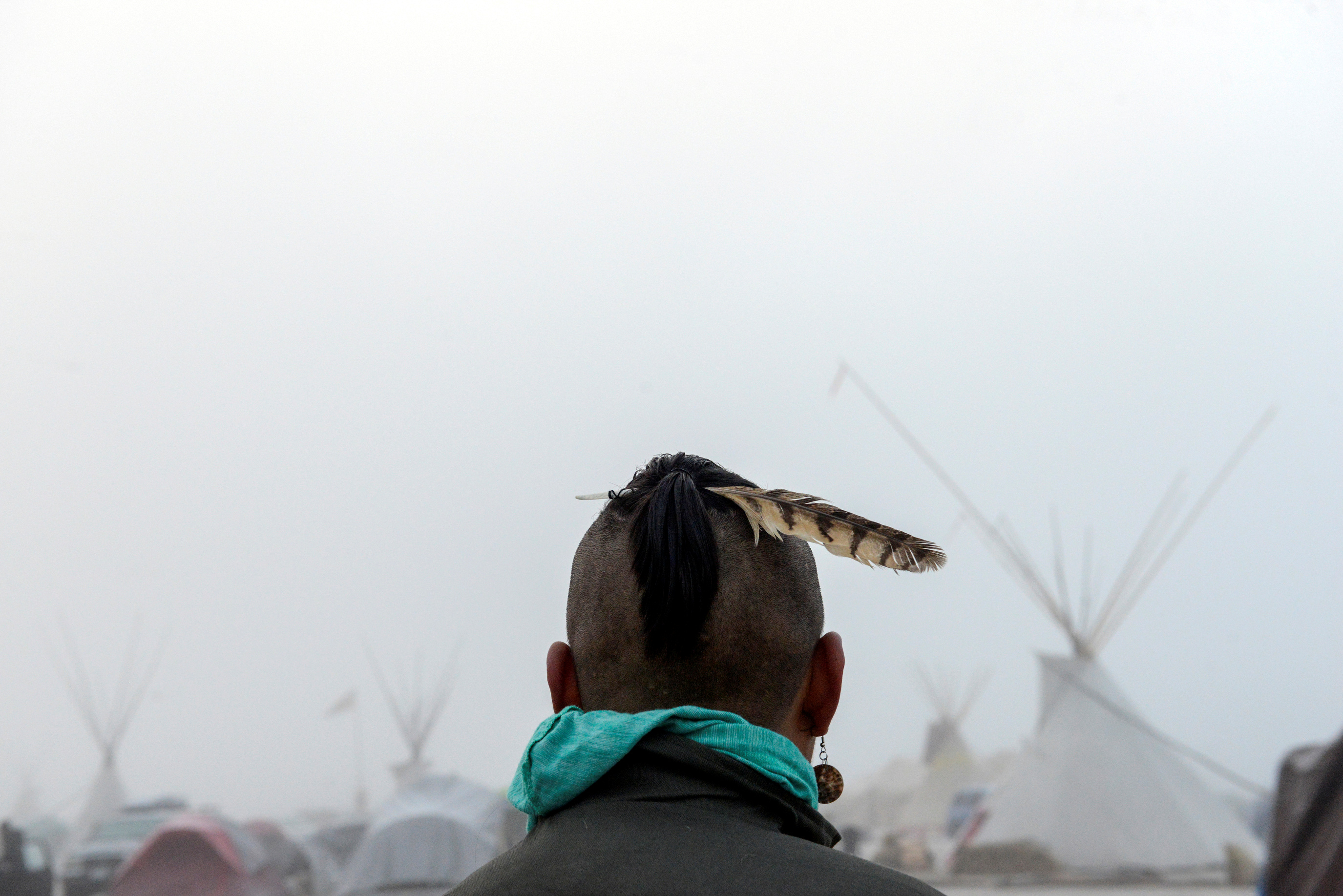 A man from the Muskogee tribe looks at the Oceti Sakowin shrouded in mist during a protest against the Dakota Access pipeline near the Standing Rock Indian Reservation.