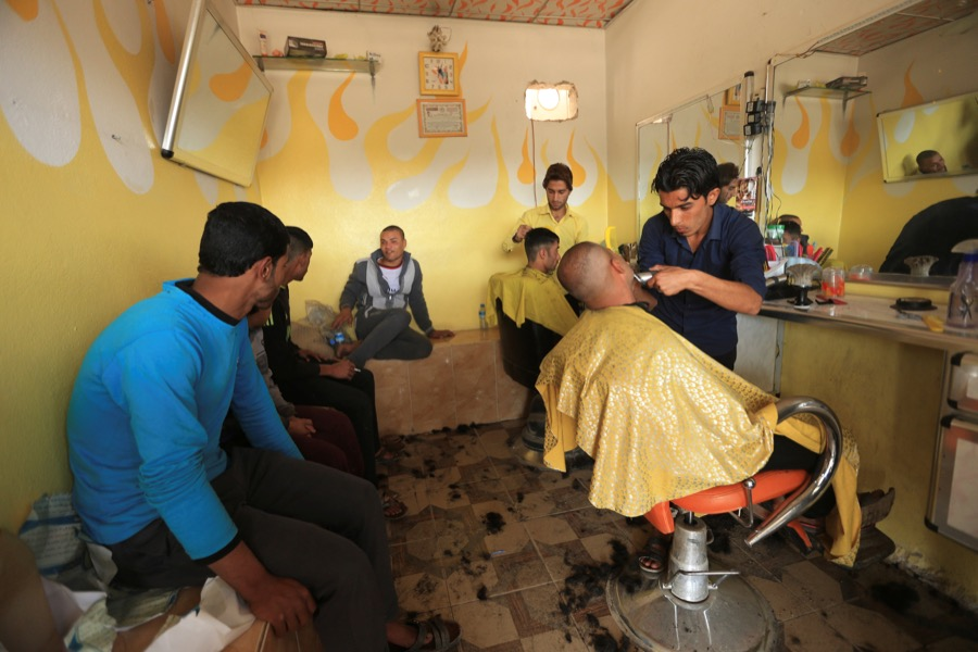 Iraqi men at a barber shop in the Intisar district of Mosul