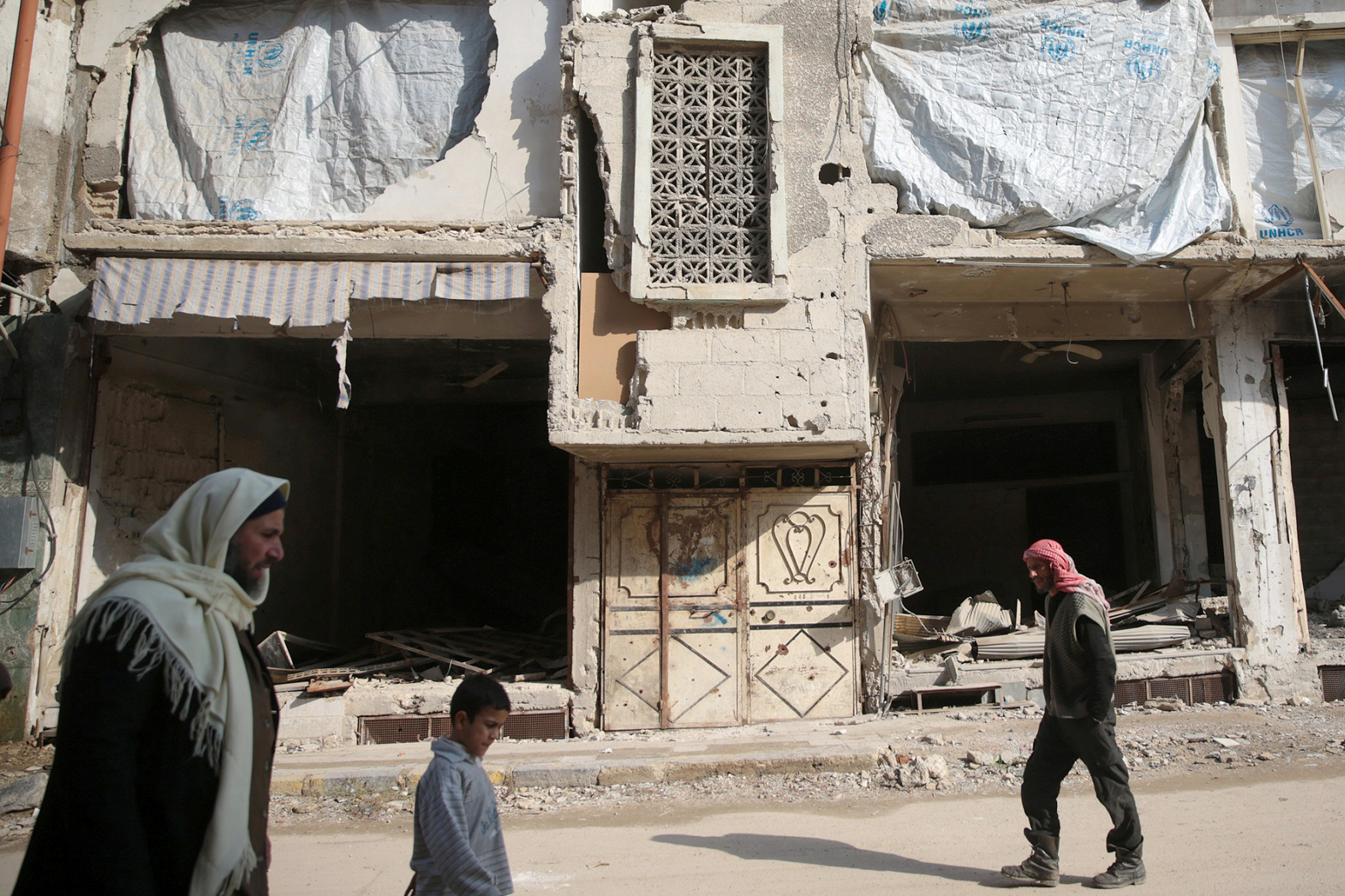 People walk past a damaged building in the eastern Damascus suburb of Ghouta, Syria.