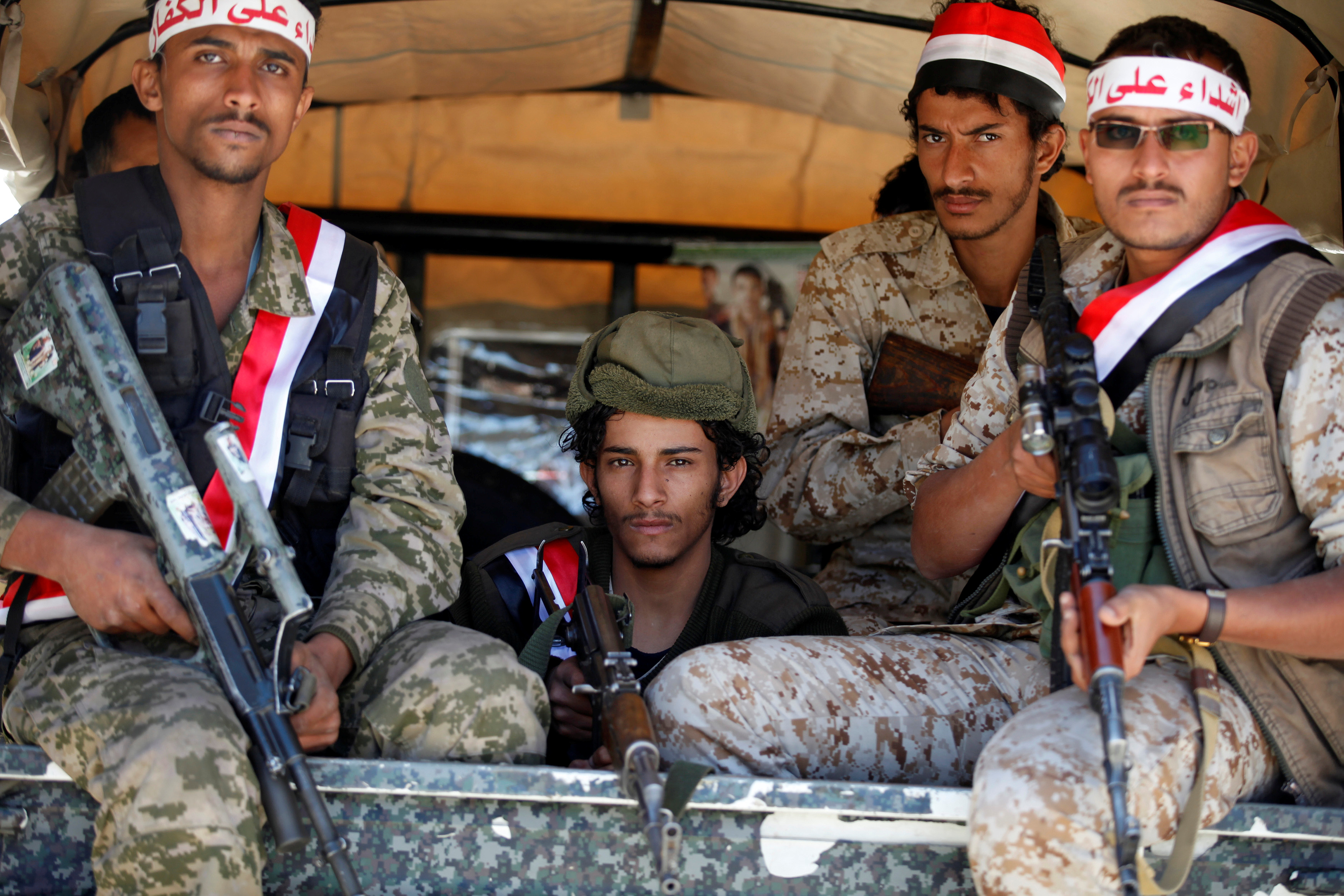Newly recruited Houthi fighters ride on the back of a pick-up truck