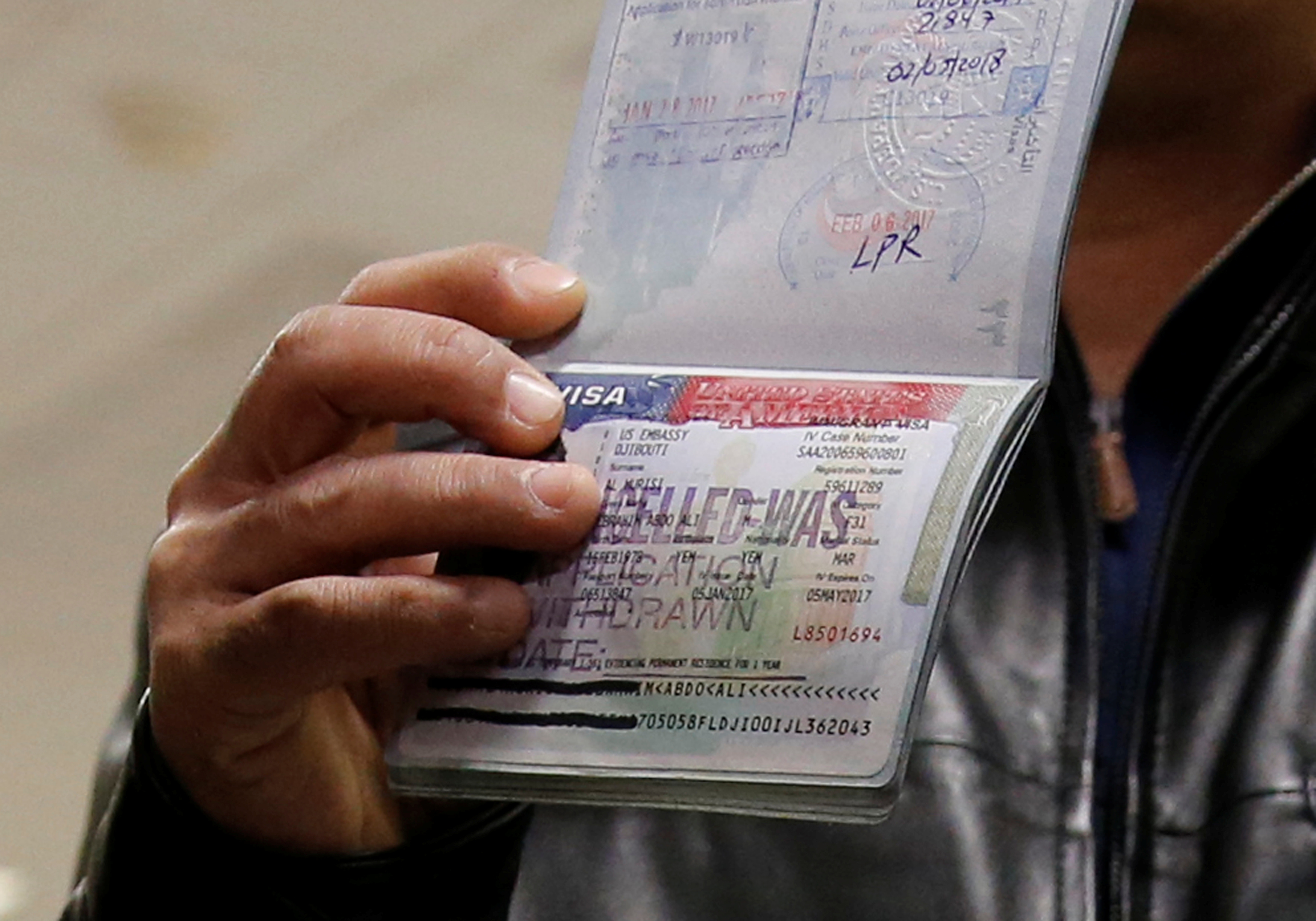 """Hand holding up passport with US visa stampend """"CANCELLED"""""""
